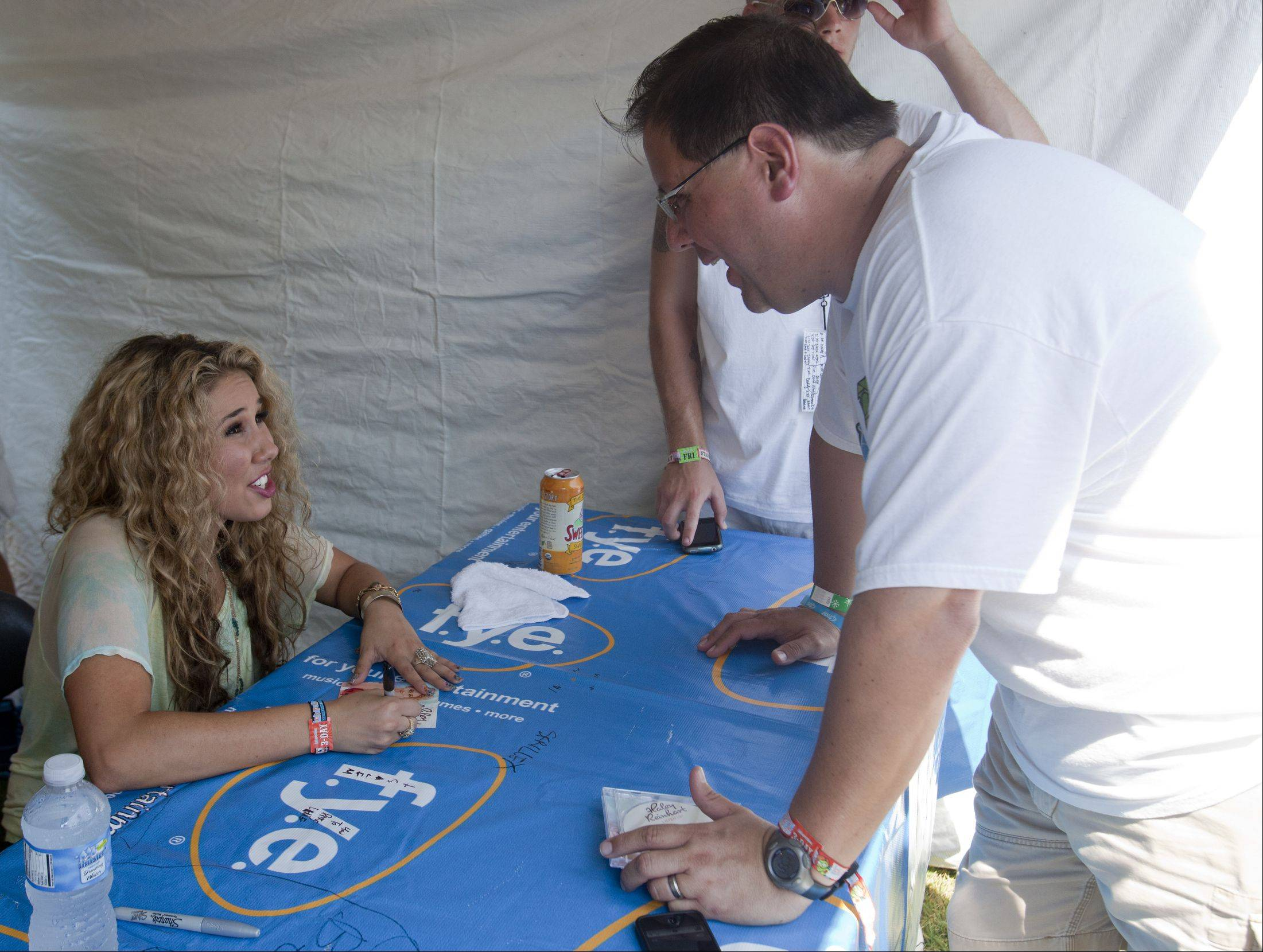 Kevin O'Neill of Bolingbrook has his Haley Reinhart CD signed during Lollapalooza in Grant Park on Friday.