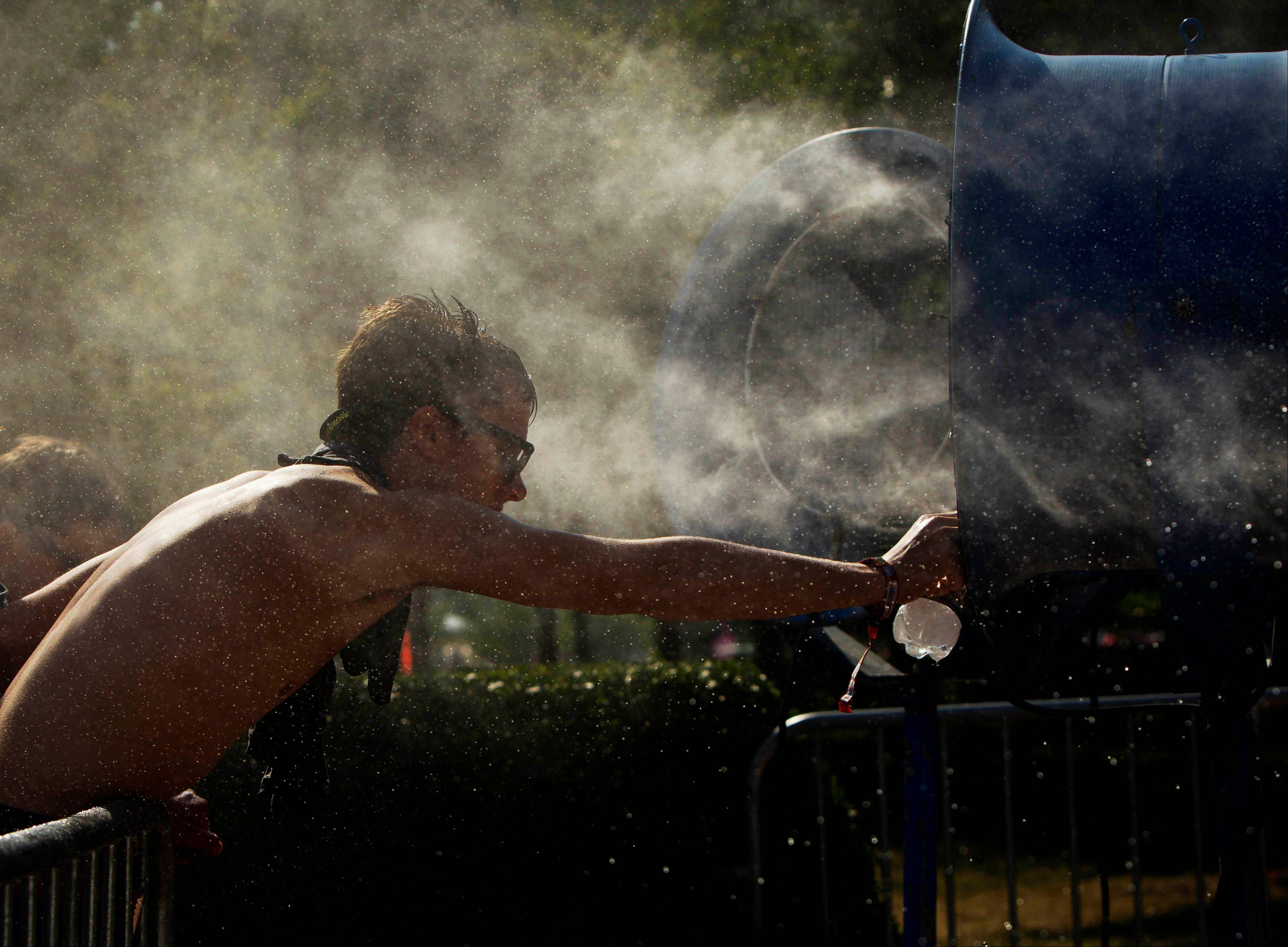 A man reaches to fill up his water bottle from a spray mist fan at Lollapalooza in Chicago's Grant Park on Friday, Aug. 3, 2012.