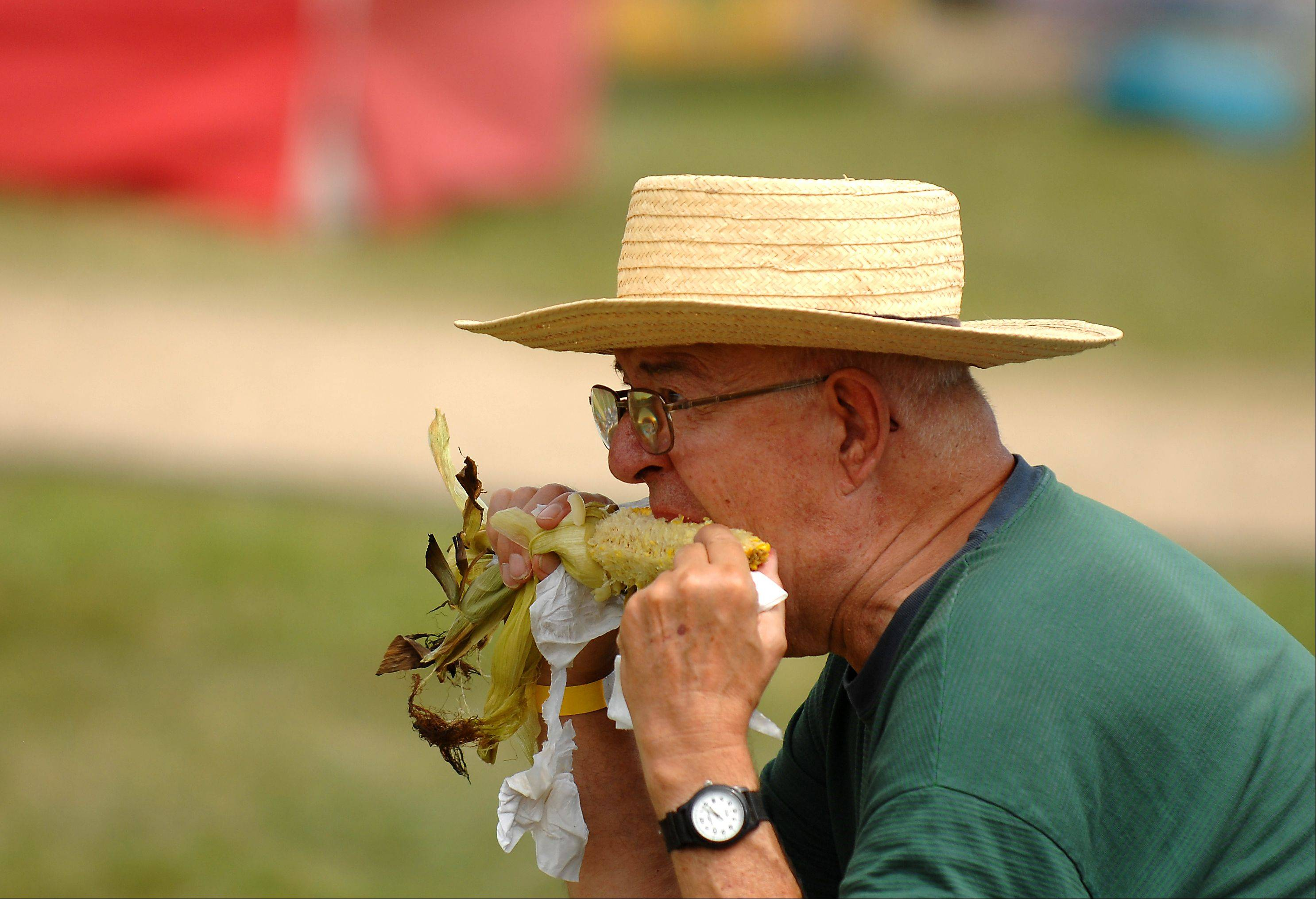 Ralph Johnson of Richmond enjoys an ear of fresh roasted corn during day two of the McHenry County Fair.