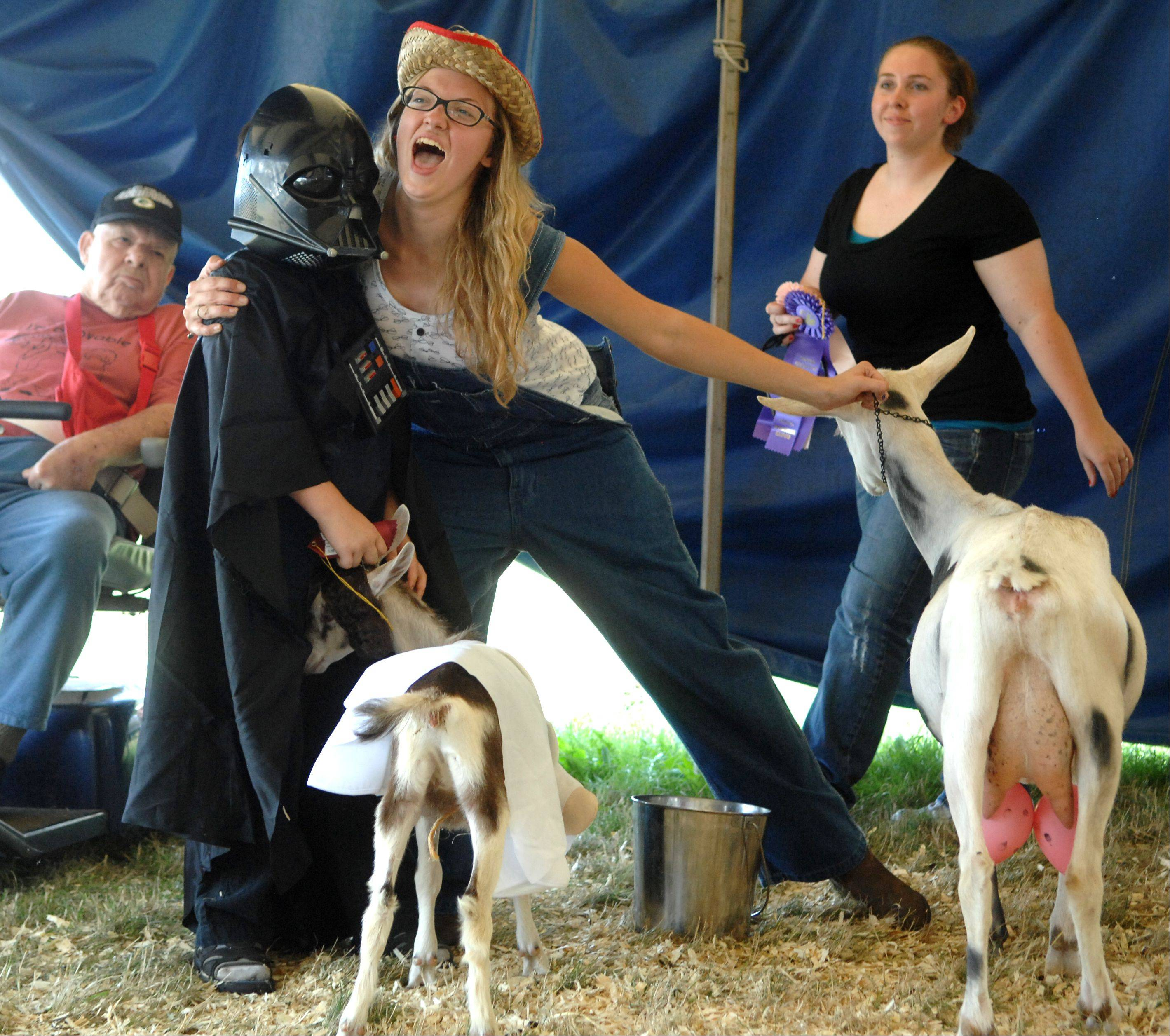 Braydin Winn, dressed as Darth Vader, 7, of Harvard gets a hug from Jordann Bauer, 19, of Lake Geneva as they hear the results of the goat costume contest during day two of the McHenry County Fair in Woodstock Thursday. Bauer won best in show with her dairy farmer costume. She painted spots on her goat and made a couple of extra udders out of balloons.