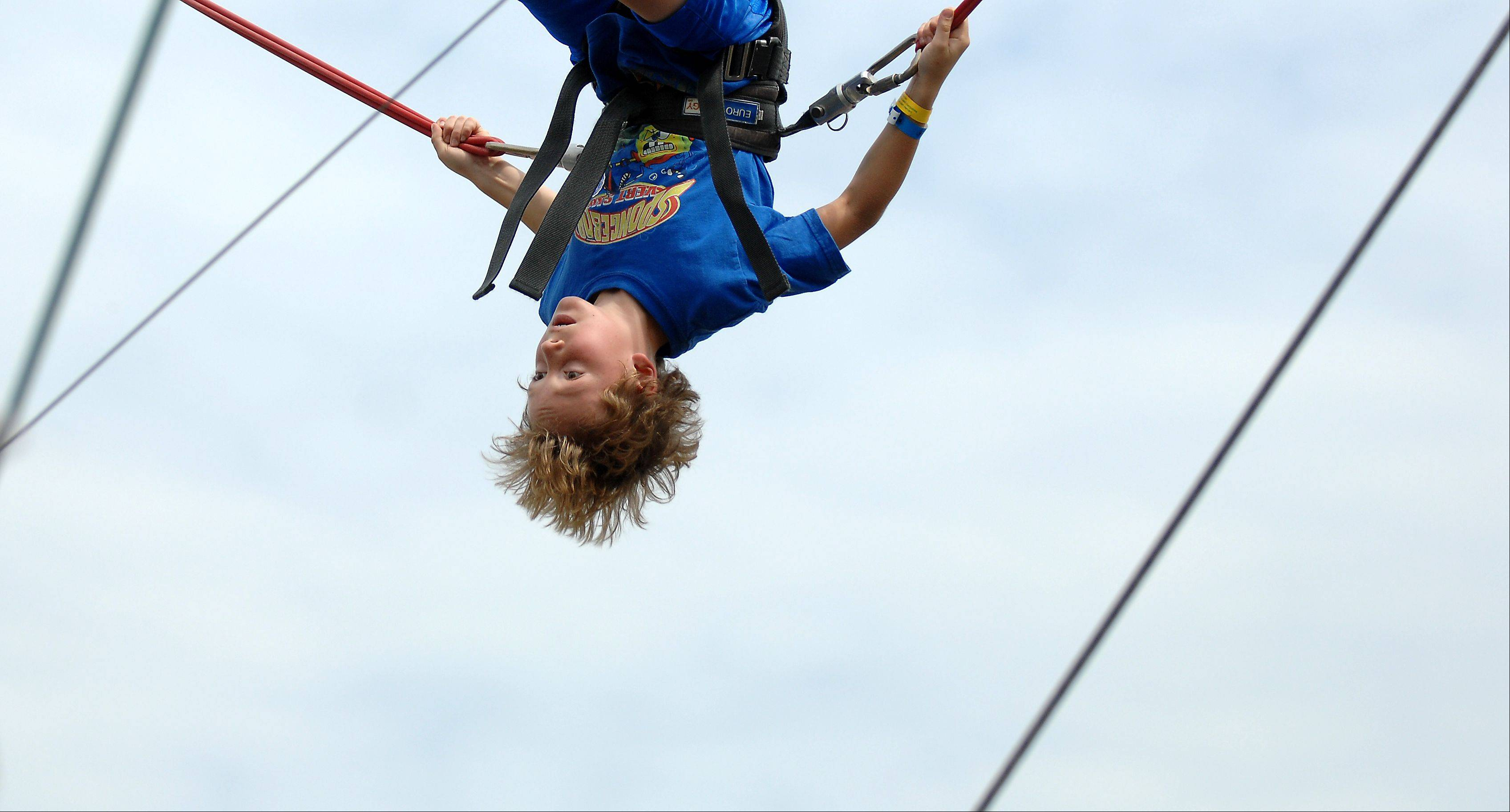 Colin McQueen, 9, of Woodstock does flips on the quad power jump during day two of the McHenry County Fair in Woodstock Thursday.