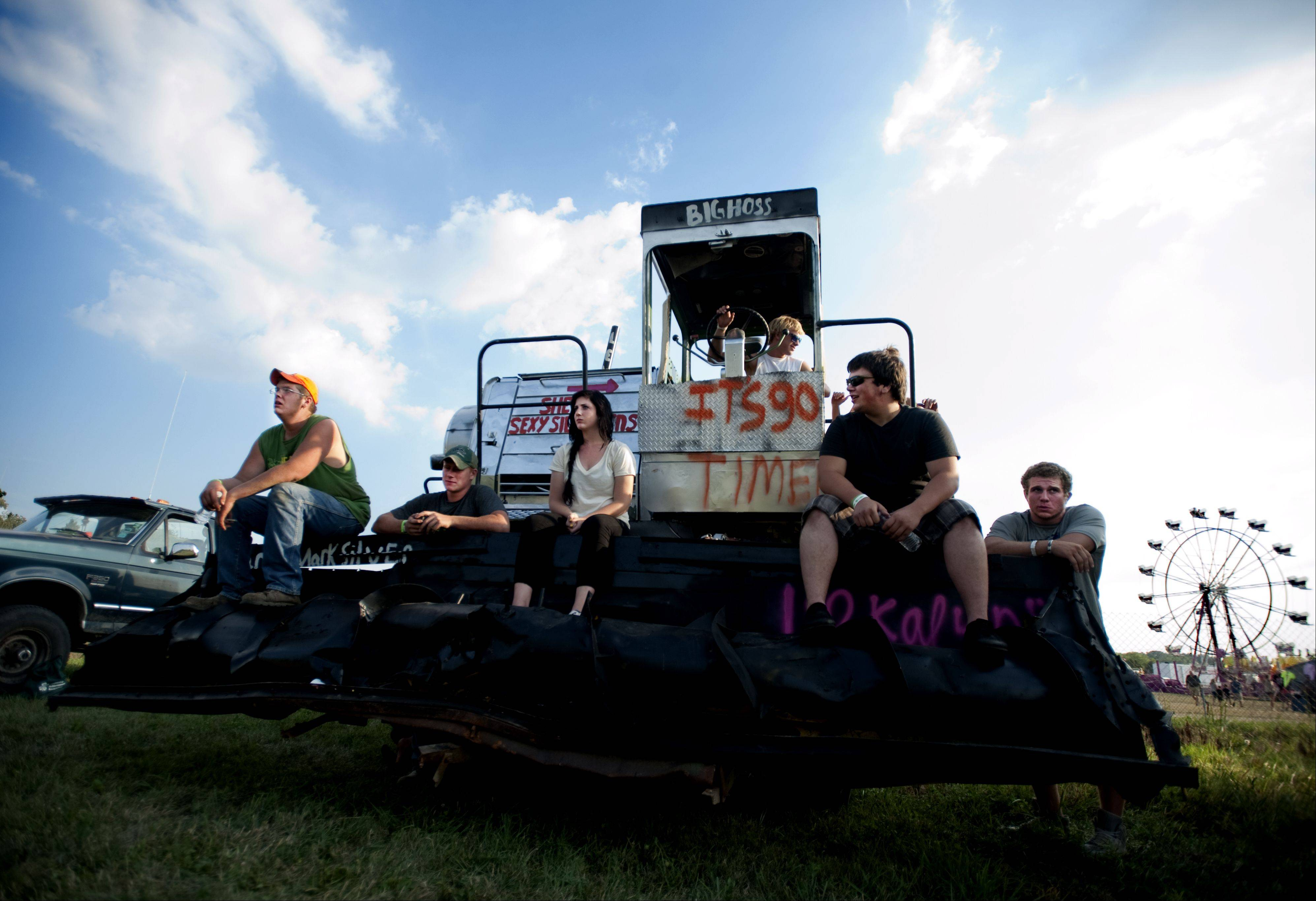 Michael Gallant, left, of Woodstock sits on his combine with friends before the Truck and Tractor Pull competition at the annual McHenry County Fair Friday in Woodstock.