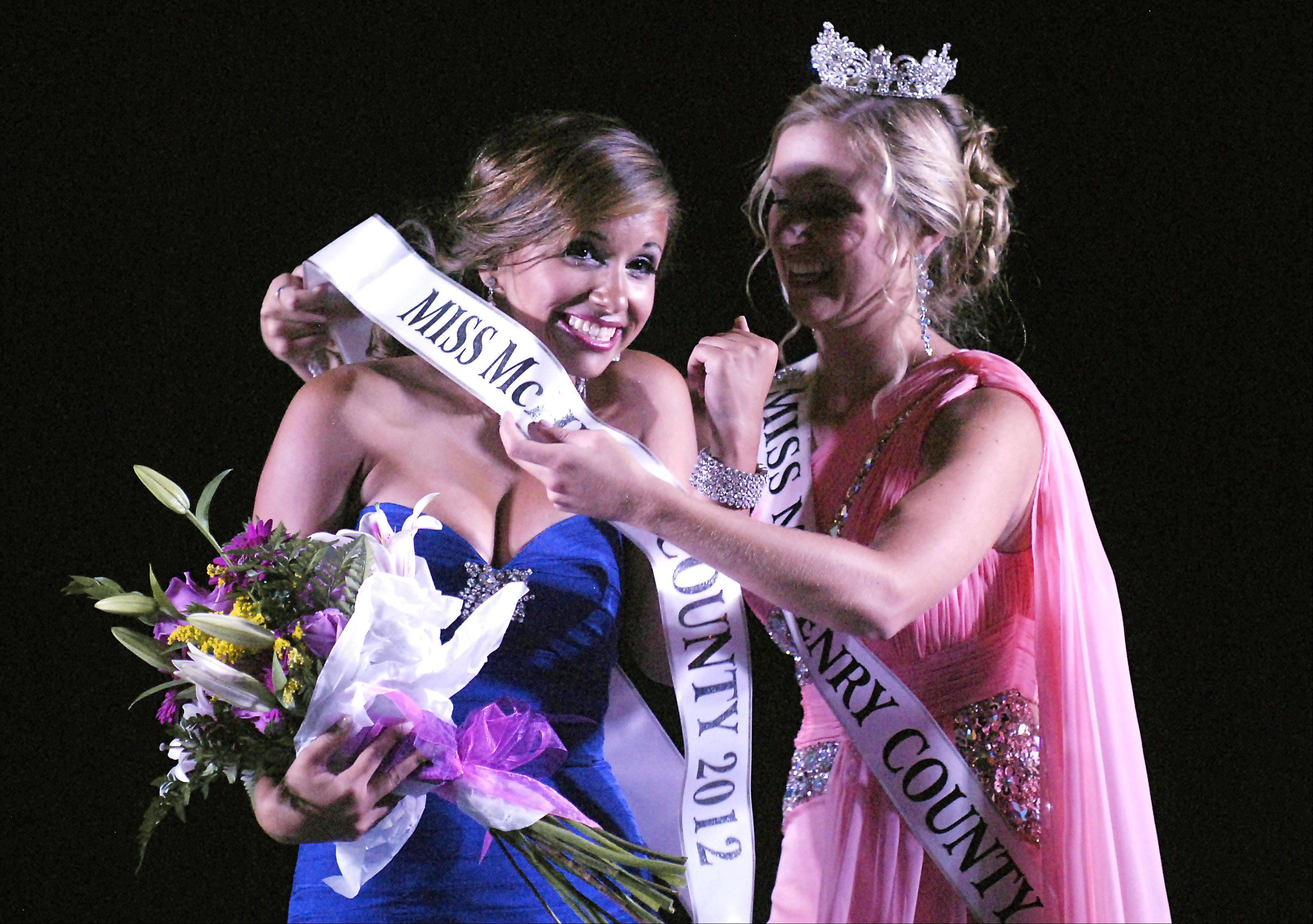 2011 McHenry County Queen Jordyn Butler helps Samantha Bolet, 17, of Lake in the Hills with her sash after Bolet was announced the 2012 Miss McHenry County.