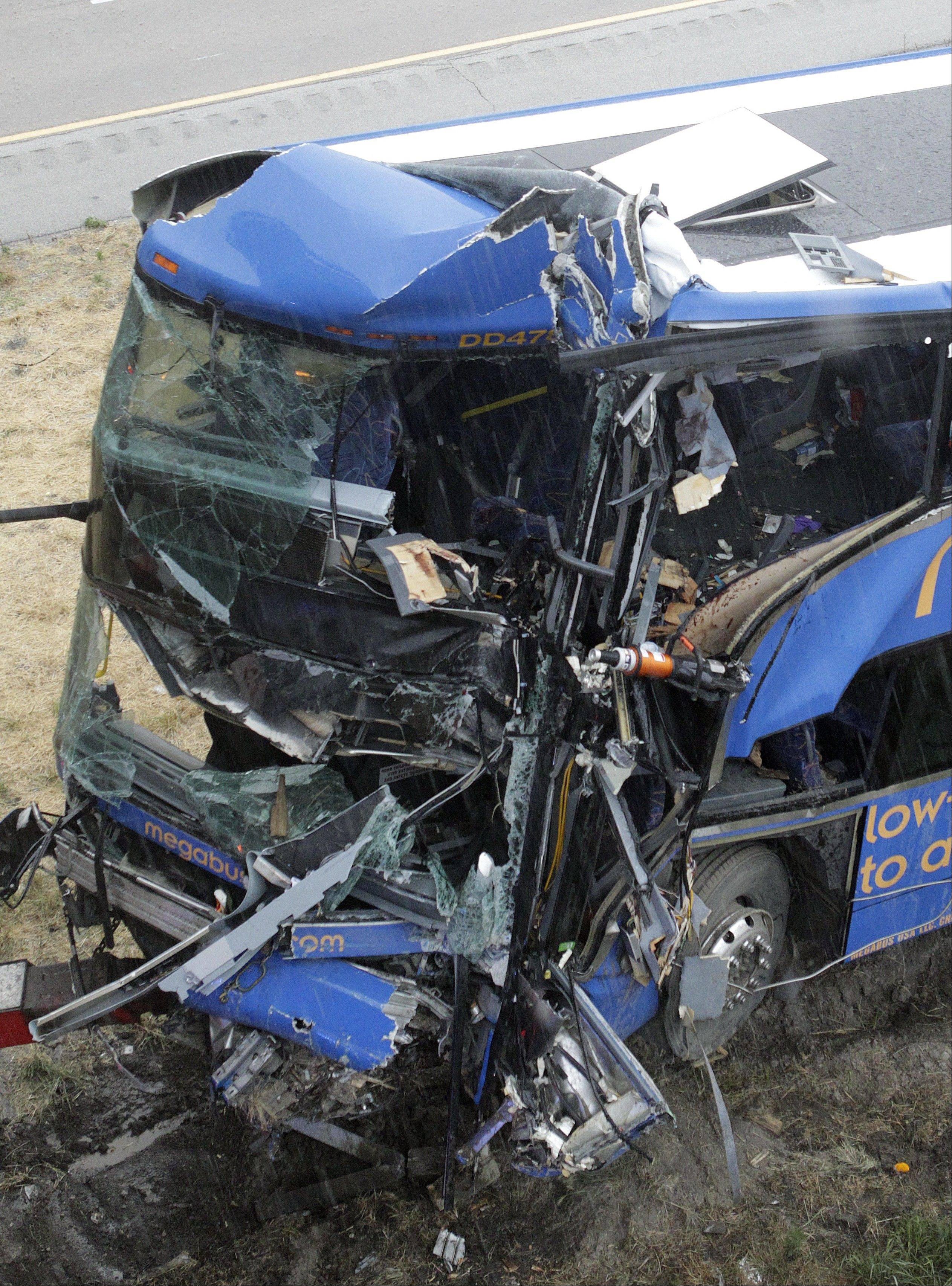 The wreckage of a Megabus is removed from the bridge support pilar that it slammed into after blowing a tire, Thursday, Aug. 2, 2012 in Litchfield, Ill. Illinois State Police Trooper Doug Francis said at least one person was killed in the afternoon wreck which was traveling from Chicago to Kansas City. He didn't immediately have other details about the death.
