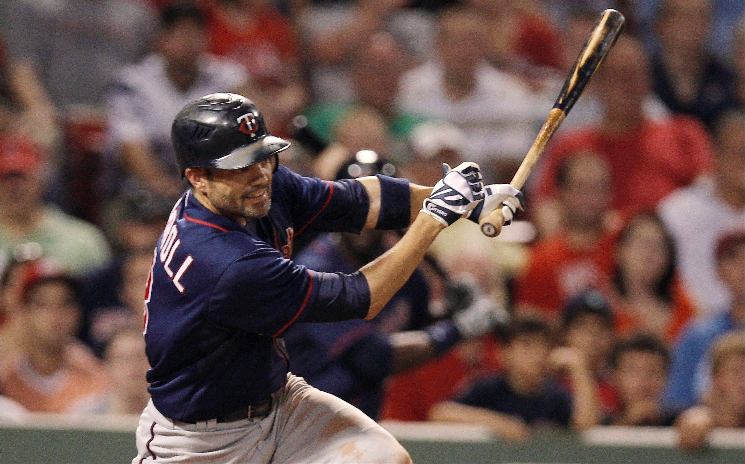 The Twins' Jamey Carroll follows through on a go-ahead RBI single during the 10th inning Friday in Boston.