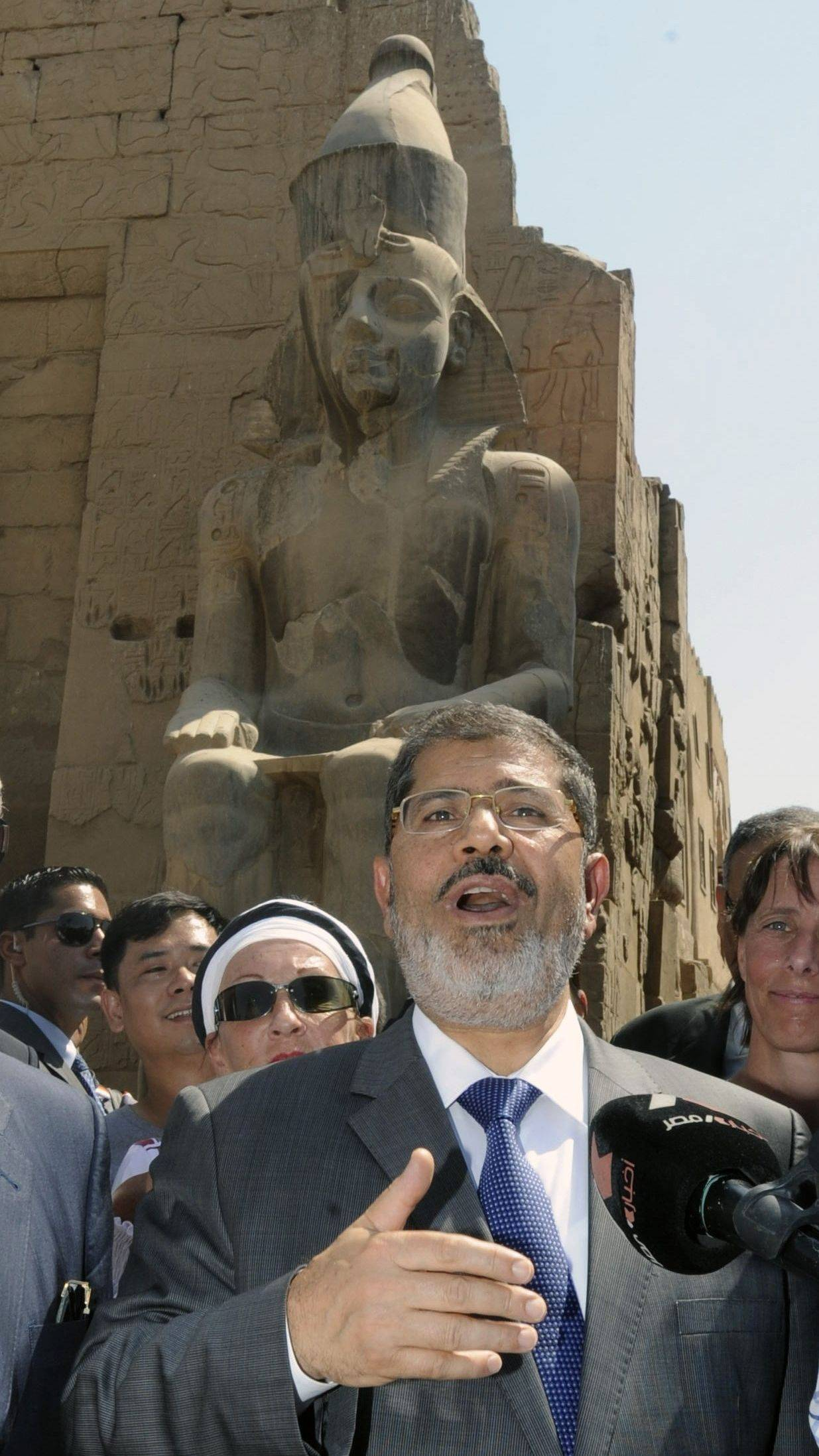 Egyptian President Mohammed Morsi, surrounded by tourists Friday, visits the Luxor temple in Luxor, Egypt. Morsi pledged to support tourism during a visit to the ancient Pharaonic temples of Luxor, a move aimed to assuage fears that the rise of an Islamist leader would undermine the country�s allure.