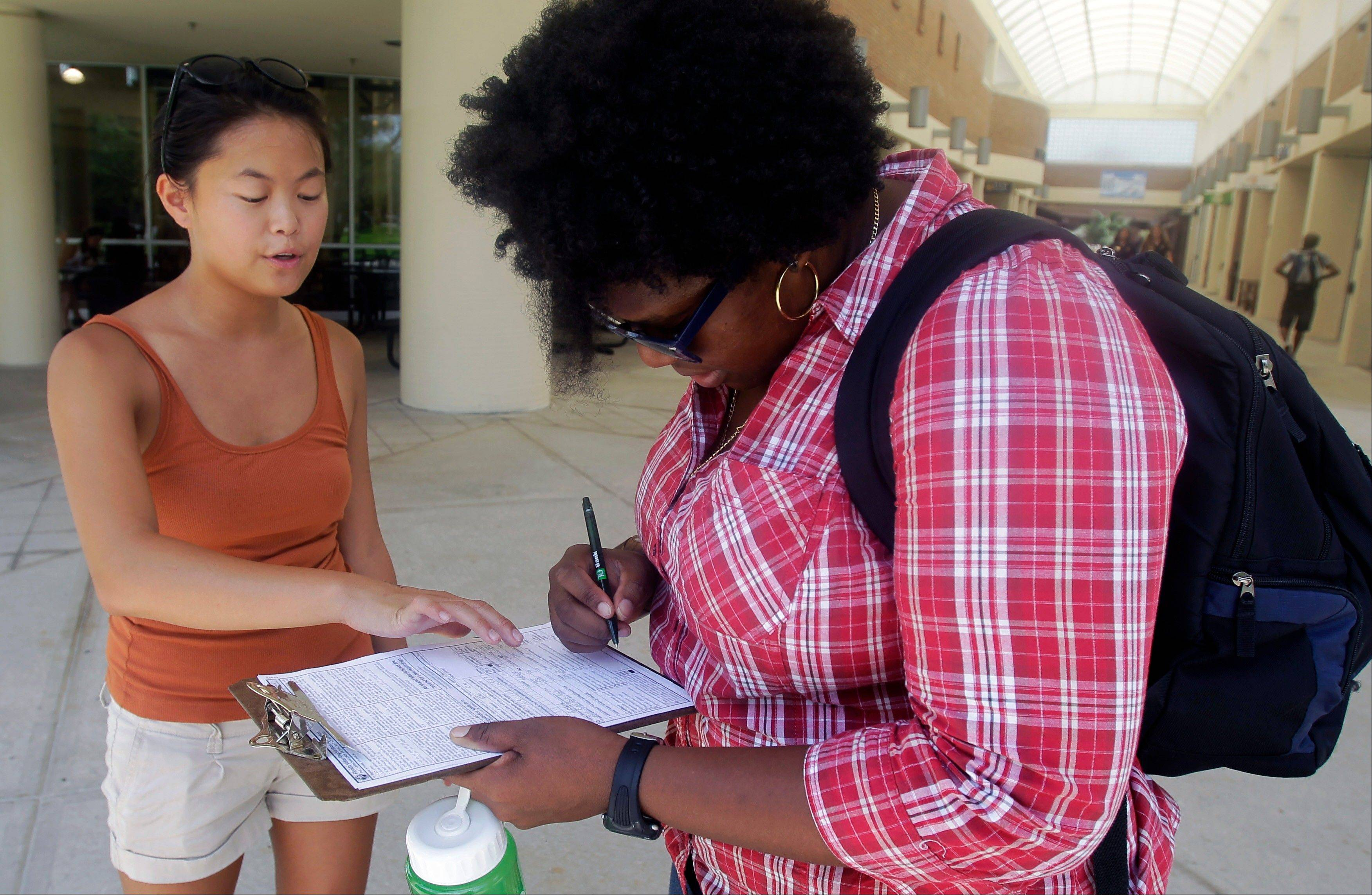 In this July 31 photo, Aubrey Marks, left, helps a University of Central Florida student to register to vote in Orlando, Fla. While most college campuses are relatively quiet, students at the University of Central Florida have taken it upon themselves to register their peers during the summer. Gone are the days when young voters weren�t taken seriously. In 2008, they helped propel Barack Obama into the Oval Office, supporting him by a 2-1 margin. But that higher profile also has landed them in the middle of the debate over some state laws that regulate voter registration and how people identify themselves at the polls.