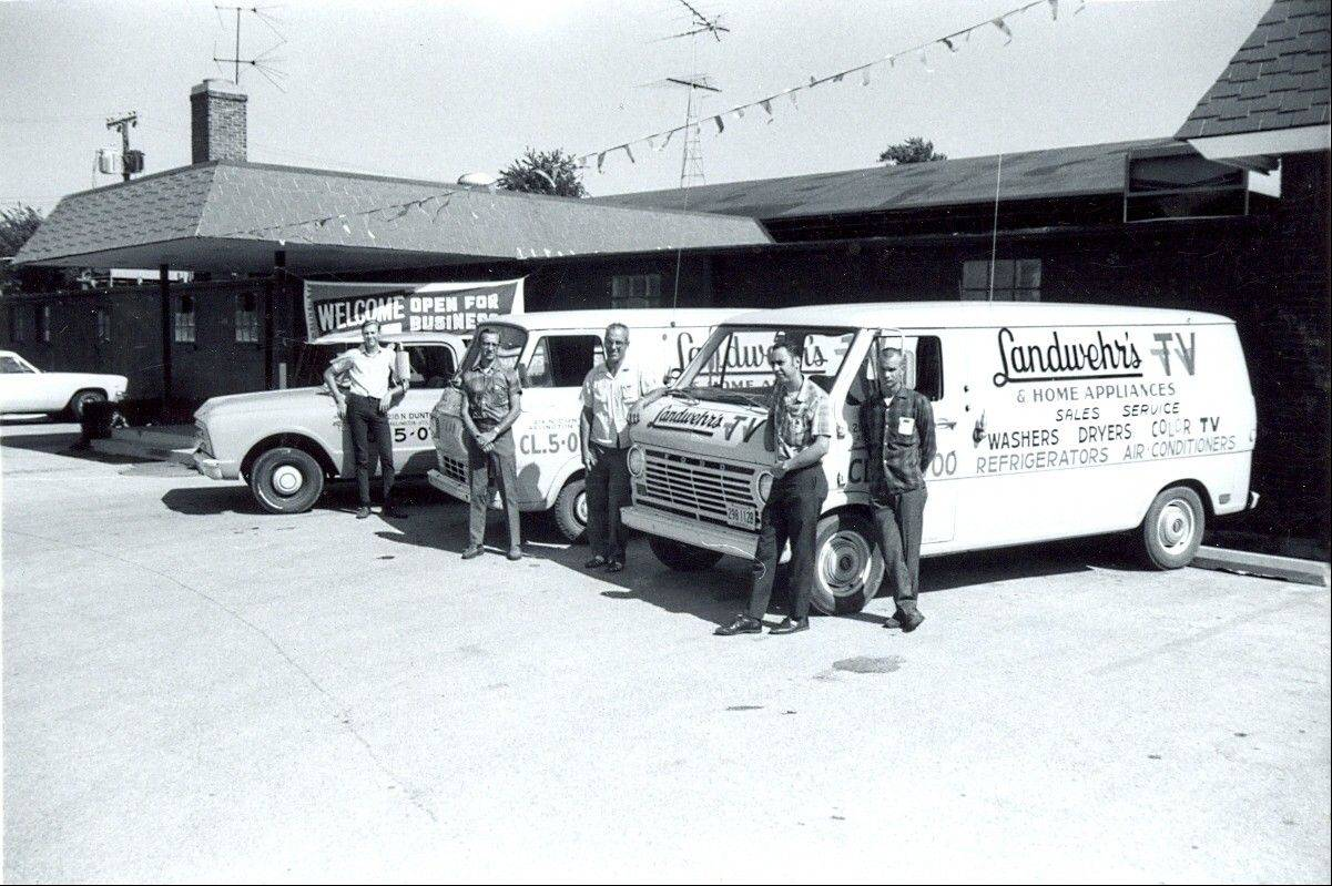Ed Landwehr, center, amid his drivers and fleet of service trucks at the Arlington Heights store, where they moved in 1969.