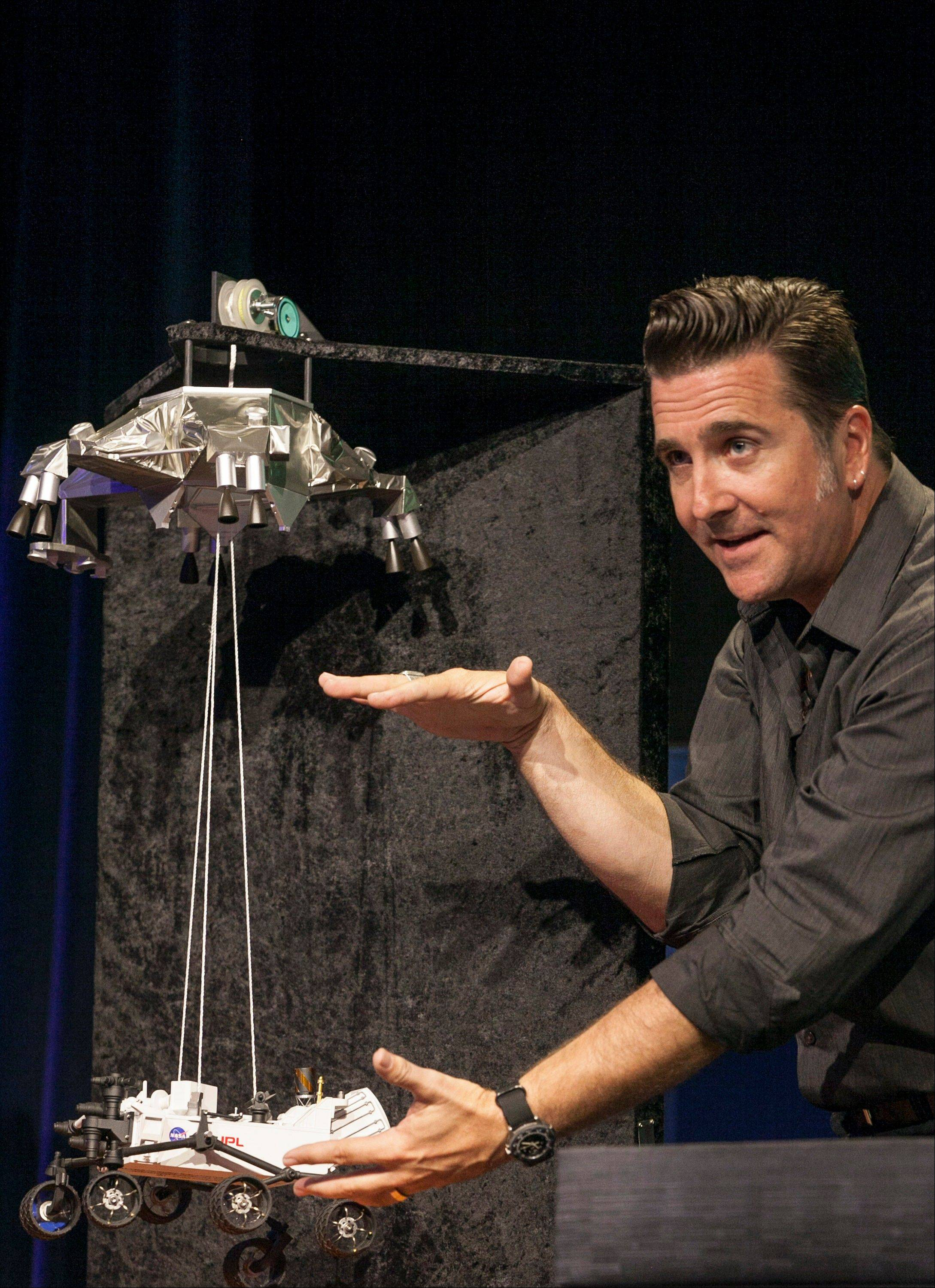 Adam Steltzner, Mars Science Laboratory's entry, descent and landing phase leader at JPL uses a scale model to explains the Curiosity rover's Entry, Descent, and Landing (EDL) during the Mission Engineering Overview news briefing at NASA's Jet Propulsion Laboratory in Pasadena, Calif. If you're planning to tune in when Curiosity lands on Mars, you'll need to know the lingo.