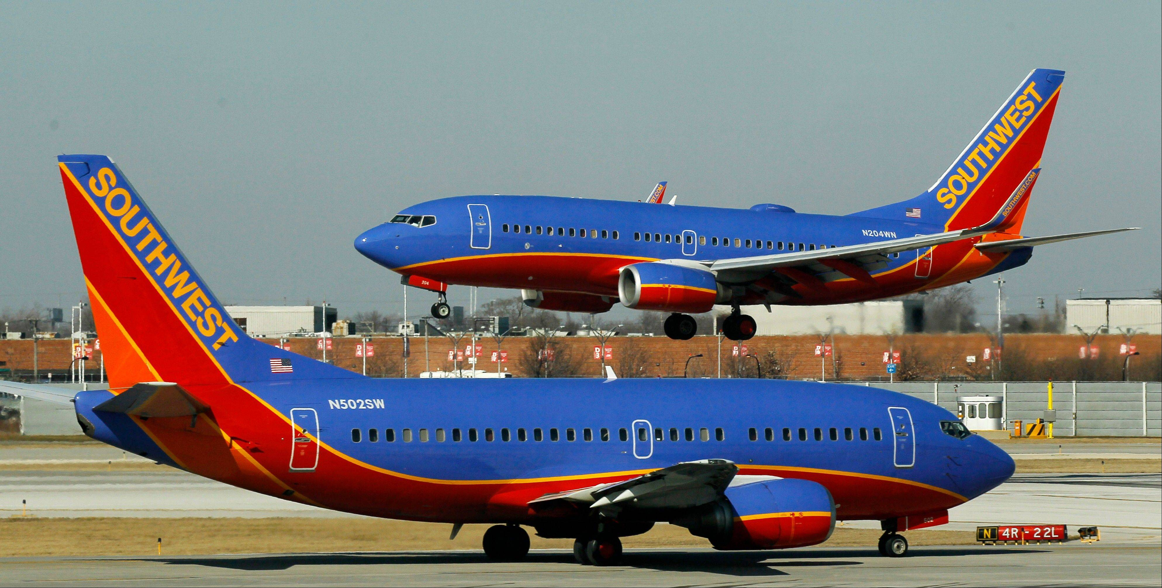 "In this Feb. 9, 2012 file photo, a Southwest Airlines Boeing 737 waits to take off at Chicago's Midway Airport as another lands. Southwest Airlines' attempt to thank its online friends with a half-price ticket sale has backfired with customers inadvertently being billed multiple times, not feeling the ""luv."" Airline spokeswoman Ashley Dillon on Saturday blamed a ""technology glitch"" for the duplicate billings to debit and credit cards."