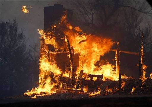 A home burns during a large wildfire Friday, Aug. 3, 2012 in Luther, Okla. A wildfire whipped by gusty, southerly winds swept through rural woodlands north and south of Oklahoma City on Friday, burning several homes as firefighters struggled to contain it in 113-degree heat.