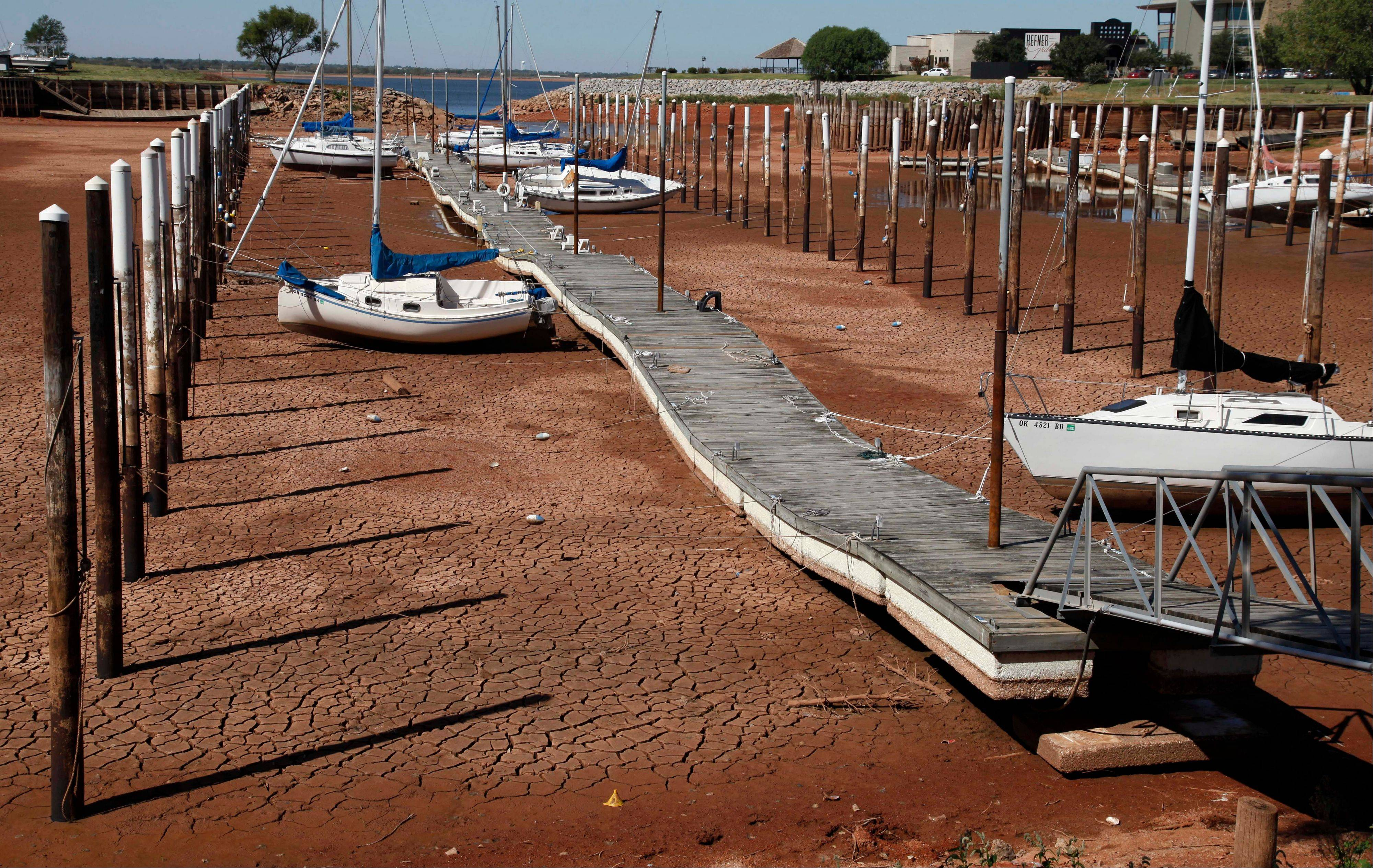 In this Sept. 30, 2011 file photo, Sailboats and a floating dock lie on the dry, cracked dirt in a harbor at Lake Hefner in Oklahoma City as drought continues to be a problem across the state. The relentless, weather-gone-crazy type of heat that has blistered the United States and other parts of the world in recent years is so rare and off-the-charts that it can't be anything but man-made global warming, a new statistical analysis from a top government scientist says.