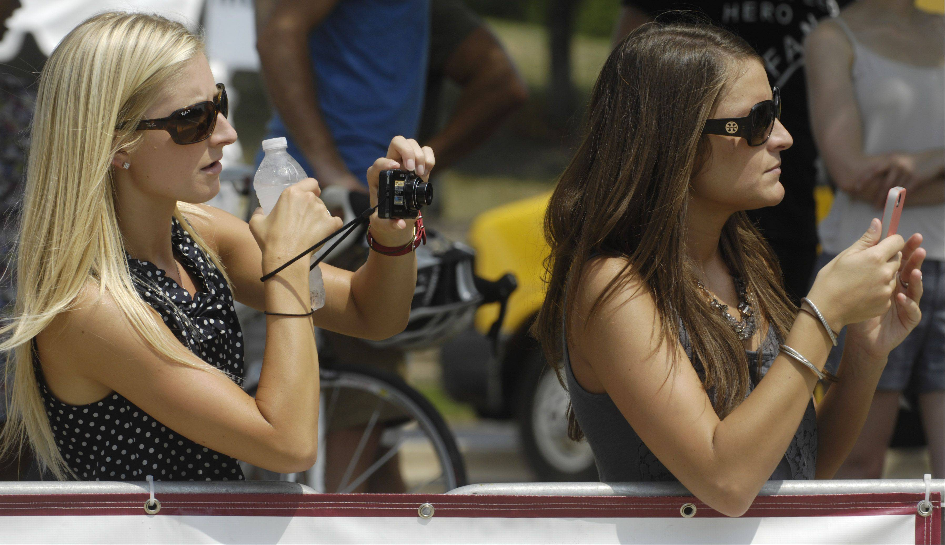 Christine Allegretti of Park Ridge and Meghan Hull of Wheaton take photos of their boyfriends, who were competing in the Tour of Elk Grove Saturday.