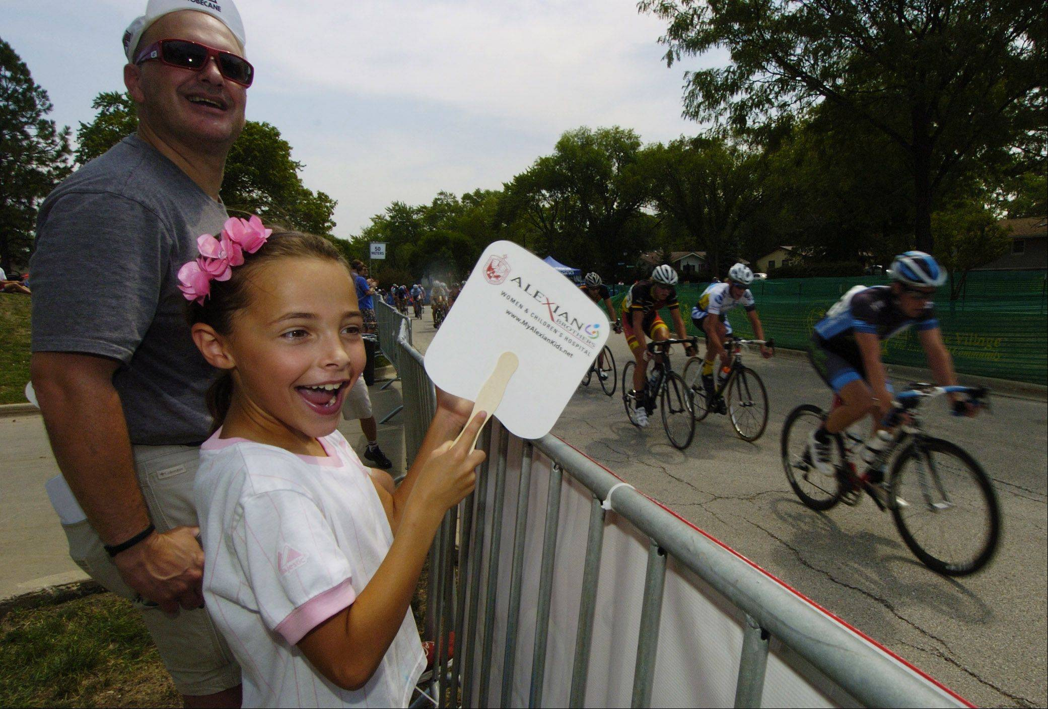Madeline Galliano, 8, of Mount Prospect and her dad, Francisco, cheer on riders during the Tour of Elk Grove Saturday.