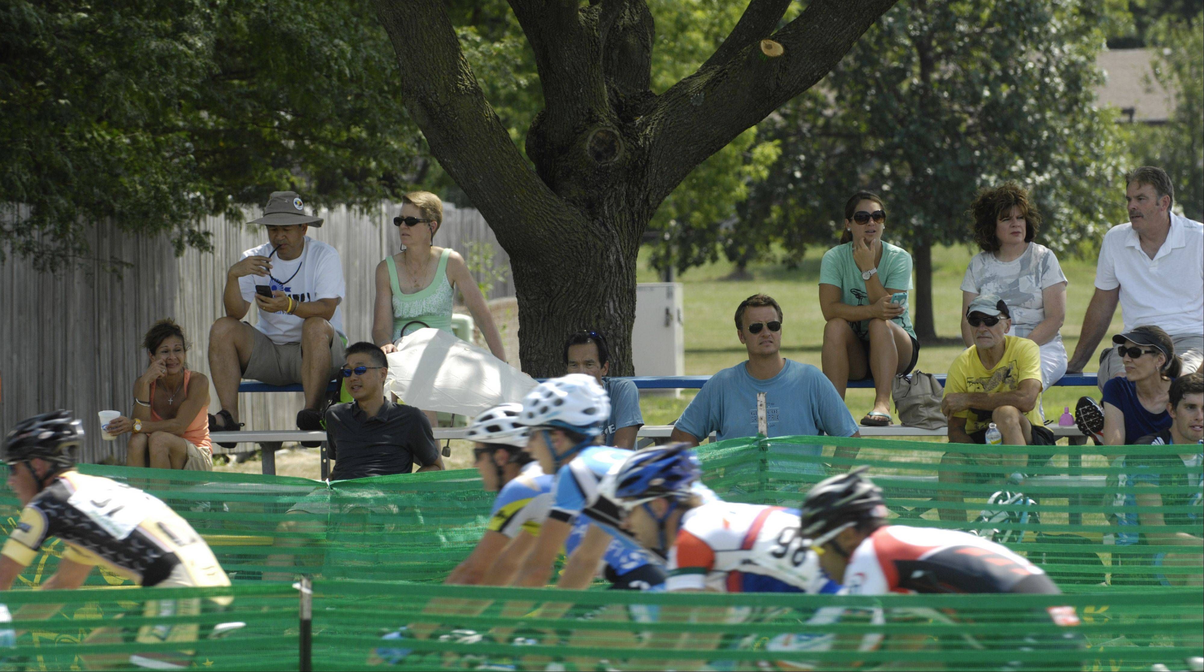 Spectators watch a bike race while seated beneath the shade of a tree during the Tour of Elk Grove Saturday.