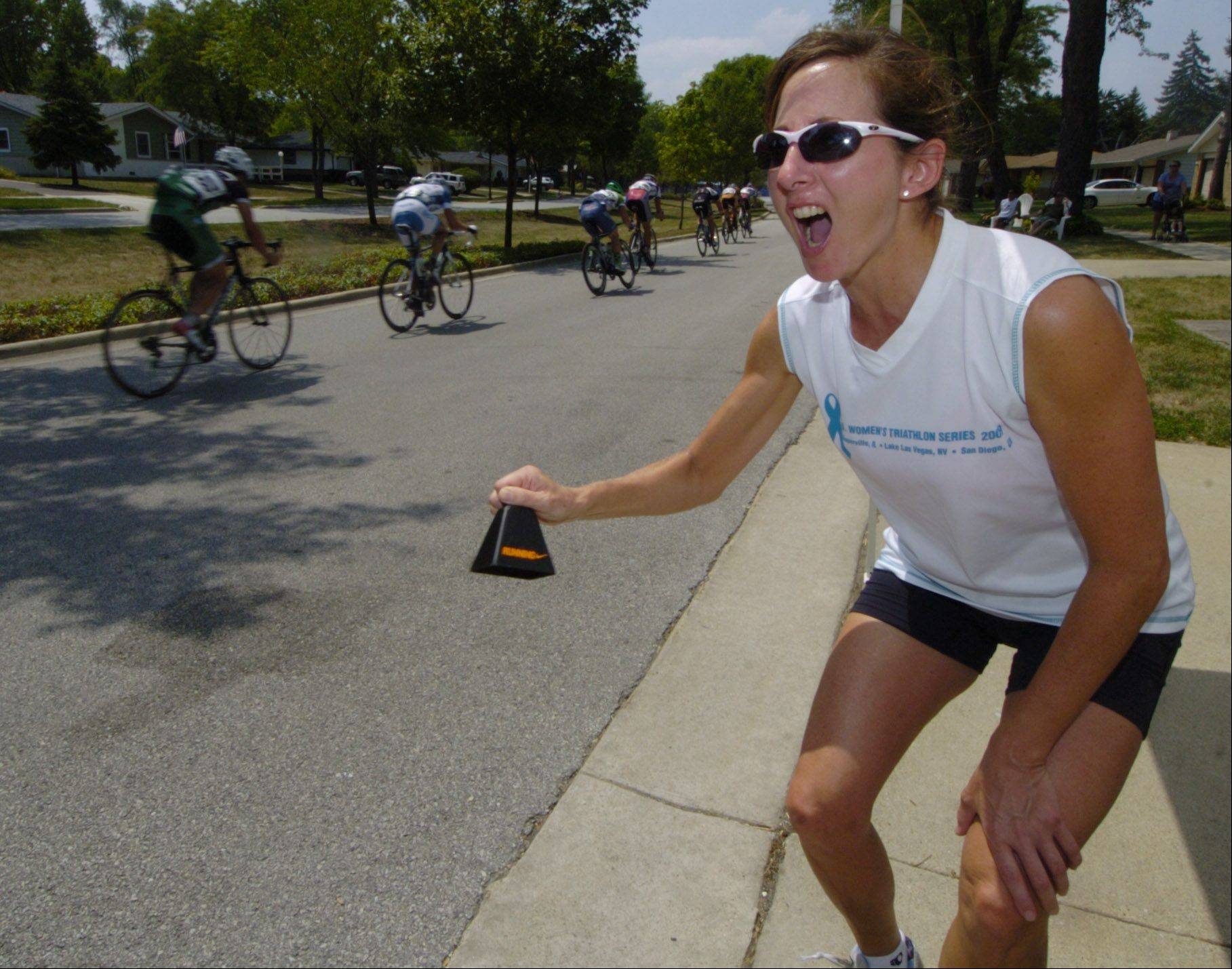 Laura Kauth of Schaumburg rings her cow bell while cheering on riders during the Tour of Elk Grove Saturday.