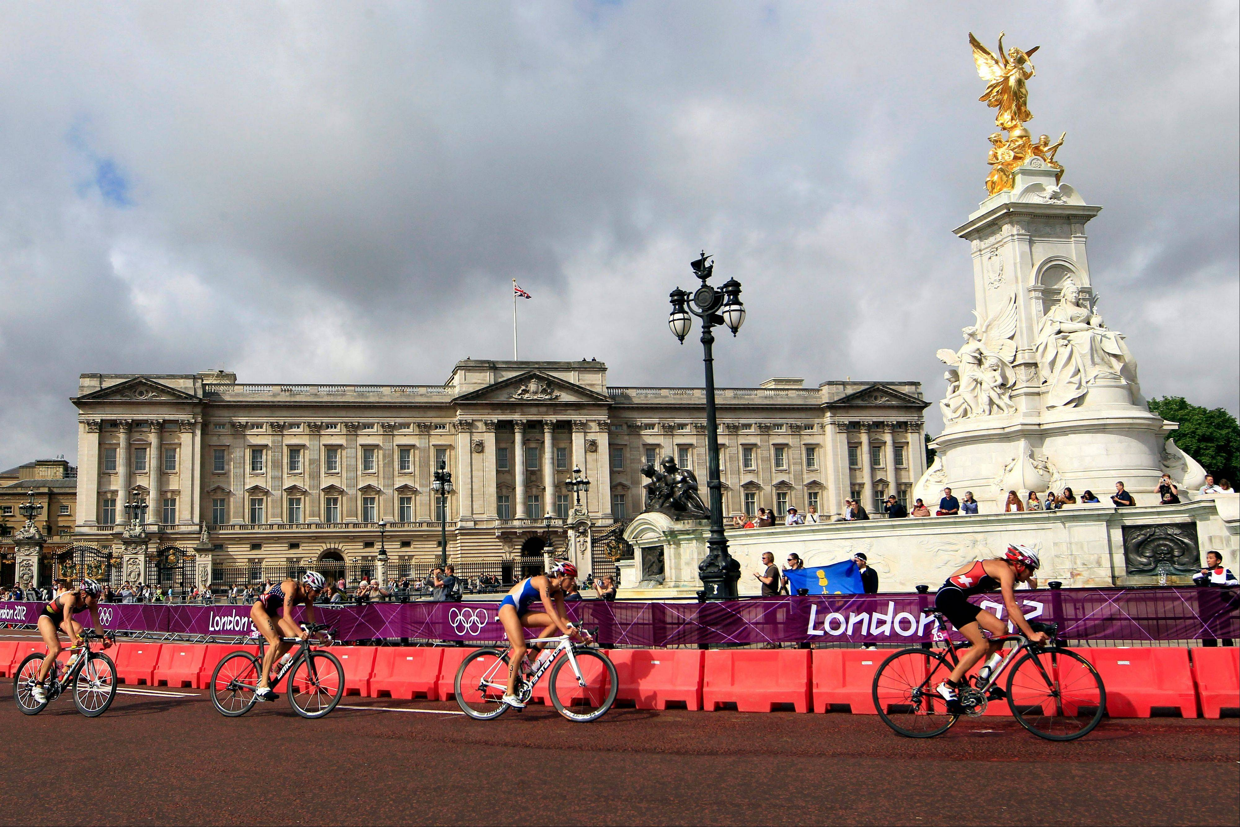 From right, Switzerland's Nicola Spirig leads Czech Republic's Radka Vodickova, United States Laura Bennett, and Germany's Svenja Bazlen pass Buckingham Palace in London during the cycling portion of the women's triathlon at the 2012 Summer Olympics, Saturday, Aug. 4, 2012.