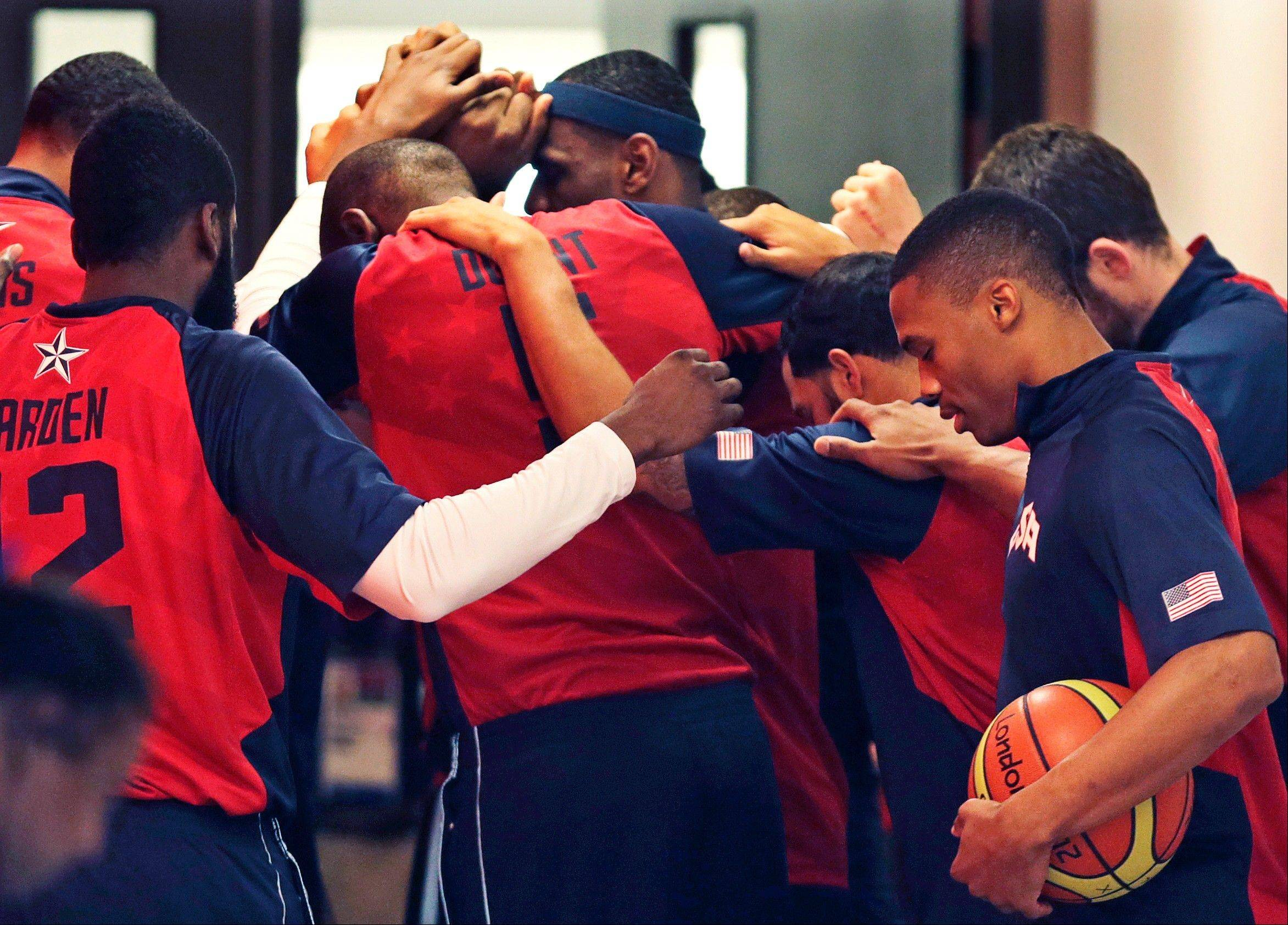 The United States team gathers around LeBron James, center with head band, prior to a men's basketball game against Lithuania at the 2012 Summer Olympics, Saturday, Aug. 4, 2012, in London.