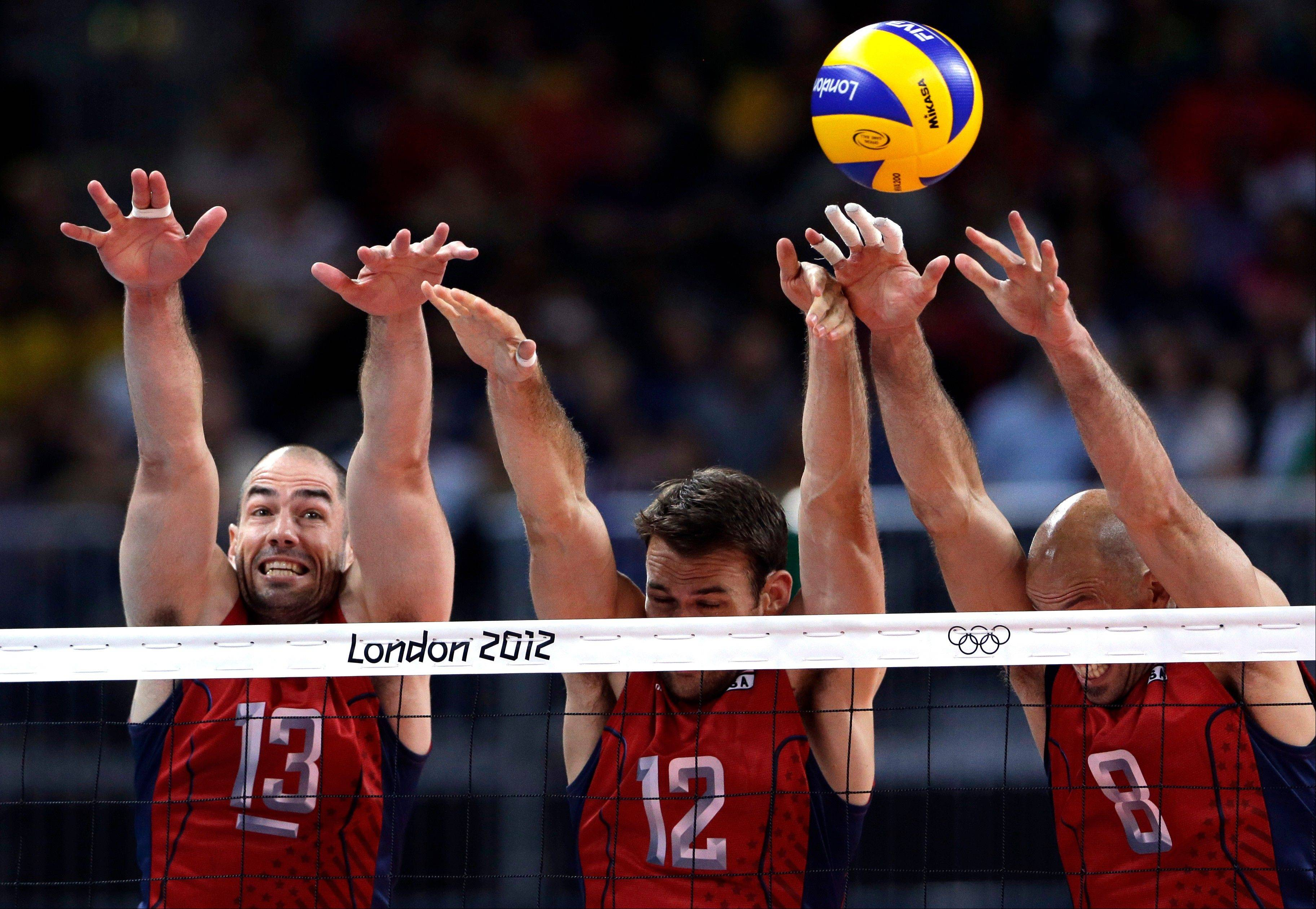 United States' Clayton Stanley, left, Russell Holmes, center, and William Priddy attempt to block a shot during a men's preliminary volleyball match against Russia at the 2012 Summer Olympics, Saturday, Aug. 4, 2012, in London.