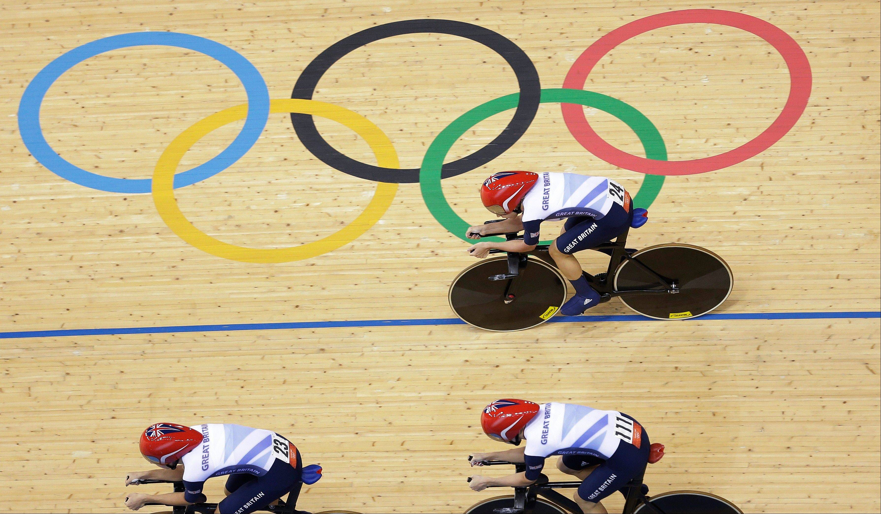 Britain's Dani King, left, leads Joanna Rowsell, bottom right, and Laura Trott to a new world record during the track cycling women's pursuit team event in the velodrome during the 2012 Summer Olympics, Saturday, Aug. 4, 2012, in London. The British women's pursuit team shattered its own world record Saturday while qualifying for the gold medal race against the United States. The team of King, Trott and Rowsell covered the 3,000 meters in 3 minutes, 14.682 seconds, lowering the mark of 3:15.669 that they set the previous day in qualifying.