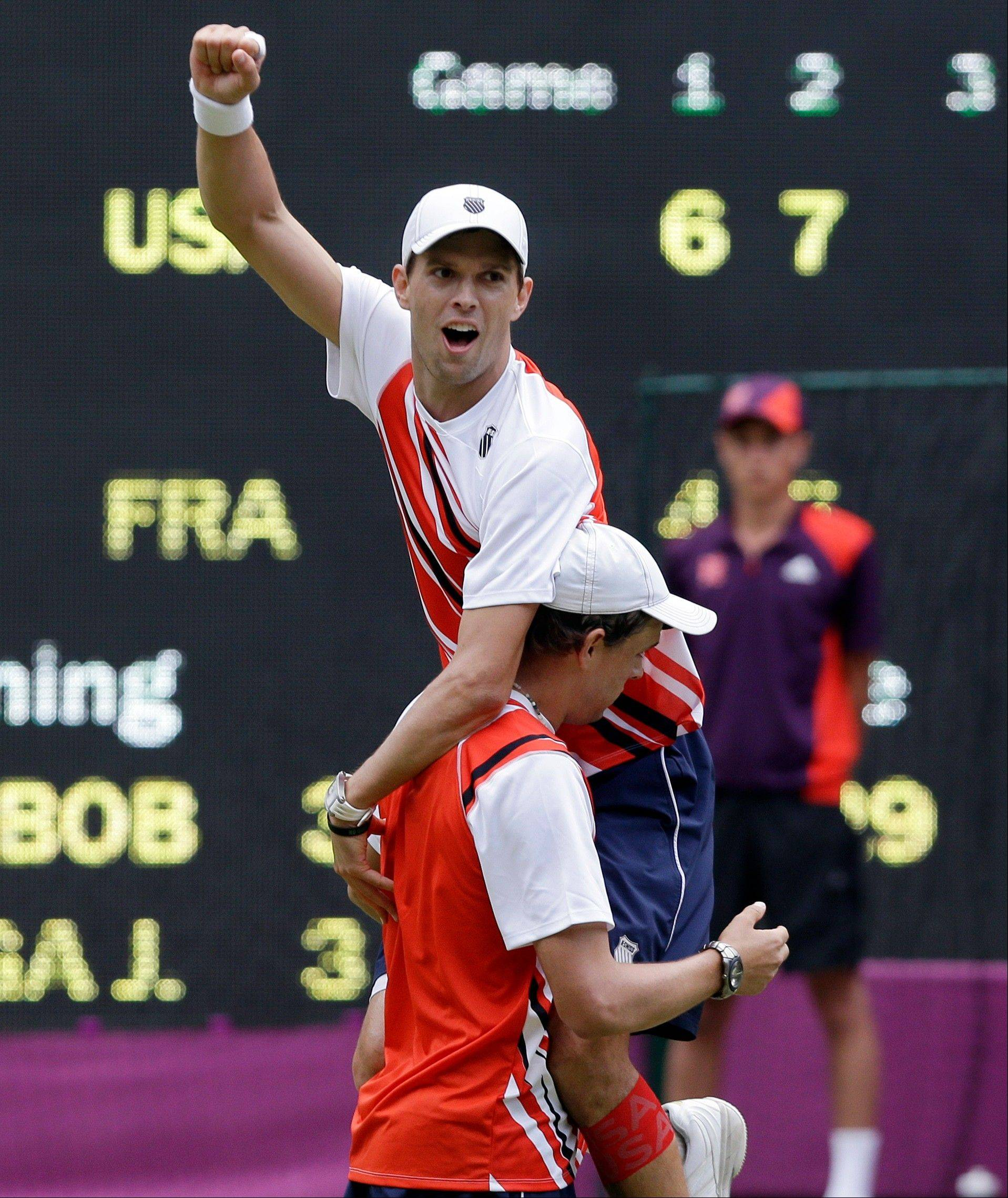 Mike Bryan, top, and Bob Bryan, bottom, of the United States, celebrate after defeating Jo-Wilfried Tsonga and Michael Llodra of France in the men's doubles gold medal match at the All England Lawn Tennis Club at Wimbledon, in London, at the 2012 Summer Olympics, Saturday, Aug. 4, 2012.