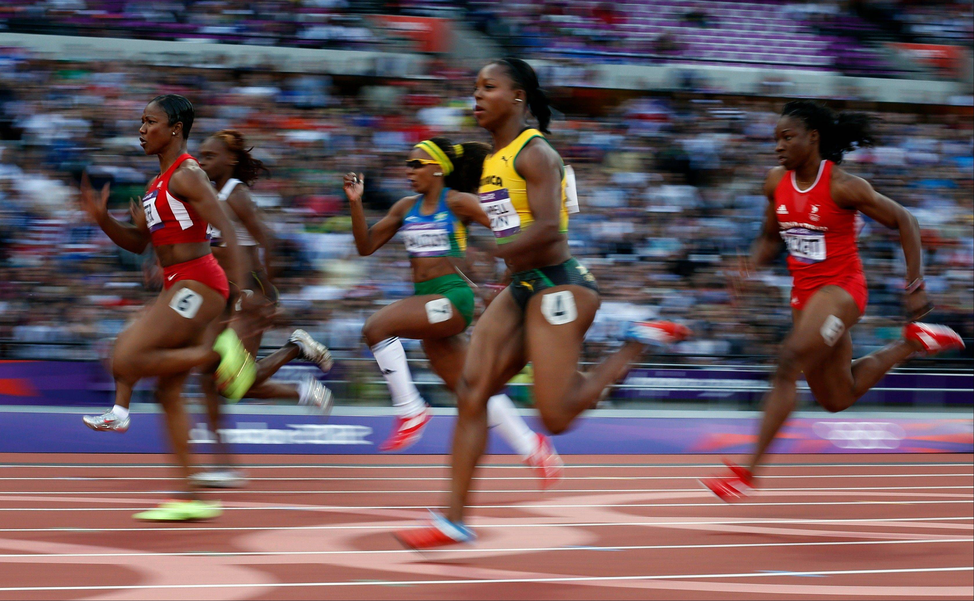 The United States' Carmelita Jeter, left, and Jamaica's Veronica Campbell-Brown, center, compete in the women's 100-meter semifinal during athletics competition in the Olympic Stadium at the 2012 Summer Olympics, Saturday, Aug. 4, 2012, in London.