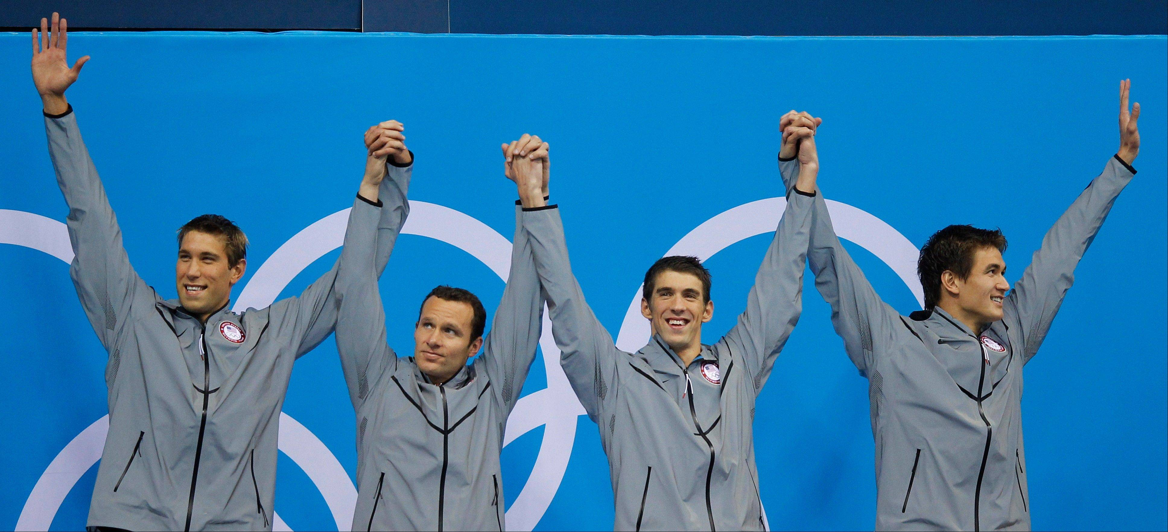 United States' men's 4 X 100-meter medley relay team from left, Matthew Grevers, Brendan Hansen, Michael Phelps and Nathan Adrian react at the Aquatics Centre in the Olympic Park during the 2012 Summer Olympics in London, Saturday, Aug. 4, 2012.