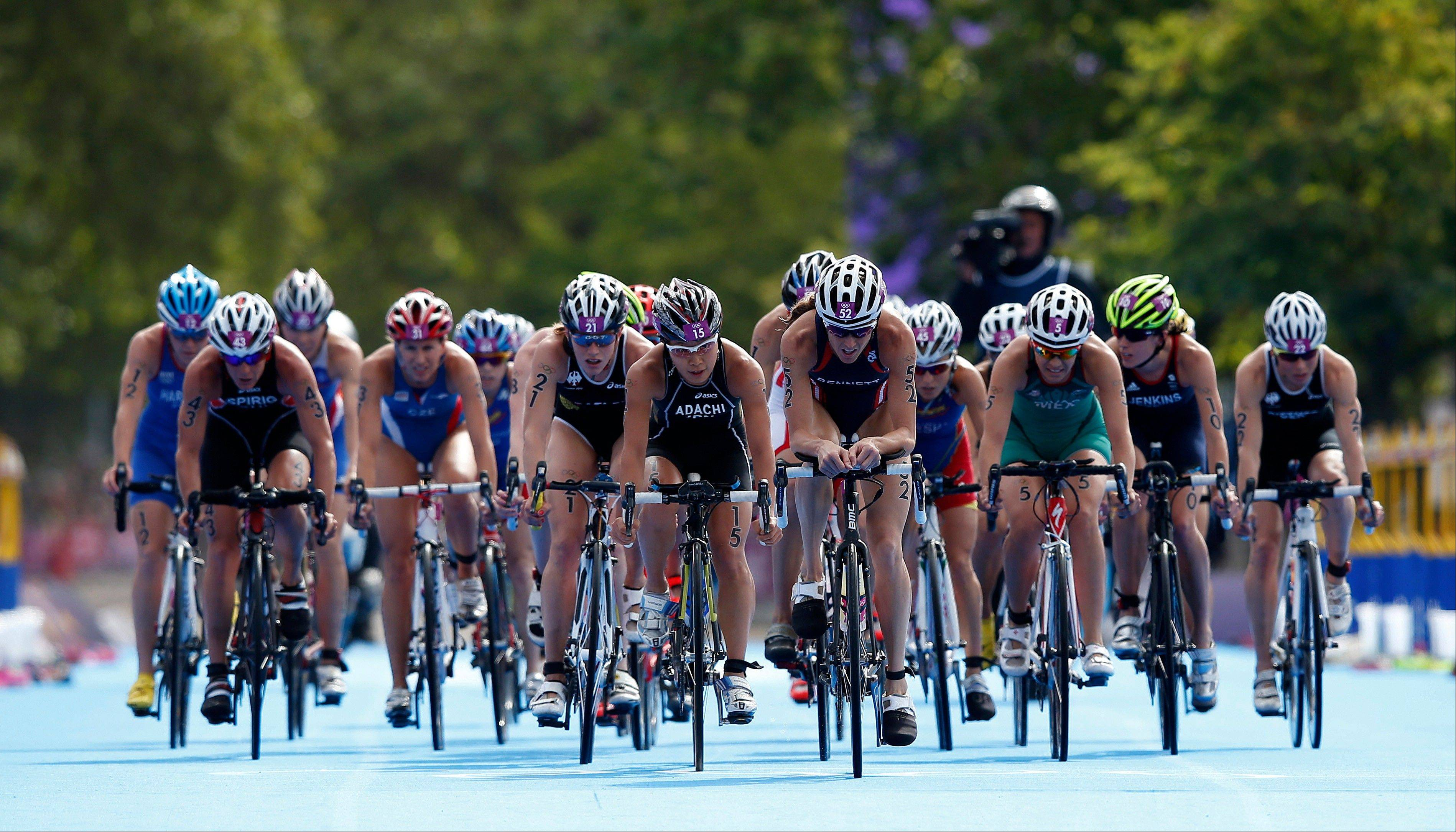 United States' Laura Bennett (52) leads a group of triathletes in the women's triathlon at the 2012 Summer Olympics, Saturday, Aug. 4, 2012, in London.