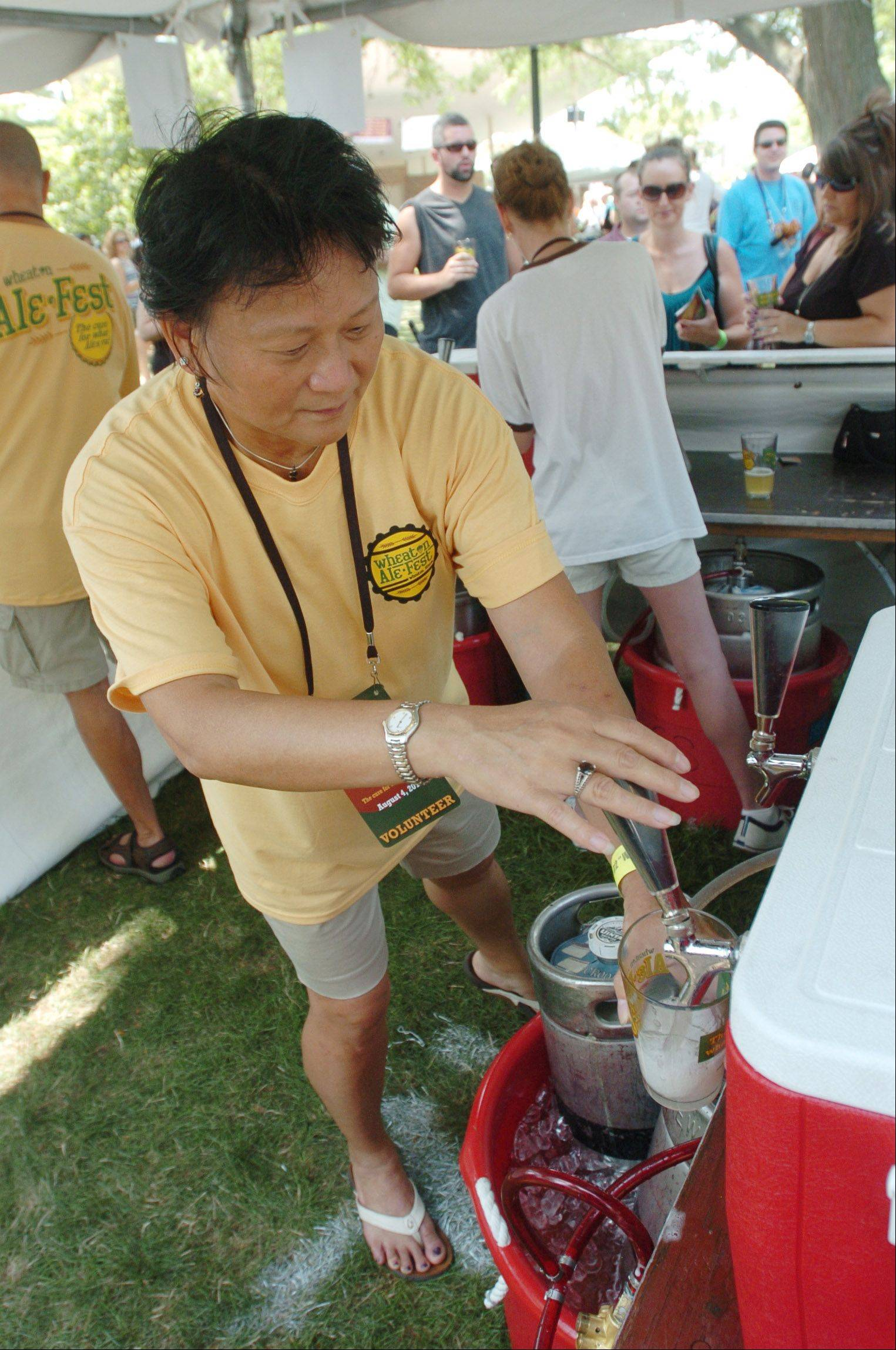 June Yoshimura of Glen Ellyn taps a keg during Wheaton Ale Fest Saturday at Memorial Park. Hundreds of brew enthusiasts sampled beers from 53 local and out-of-state breweries at the second annual event.
