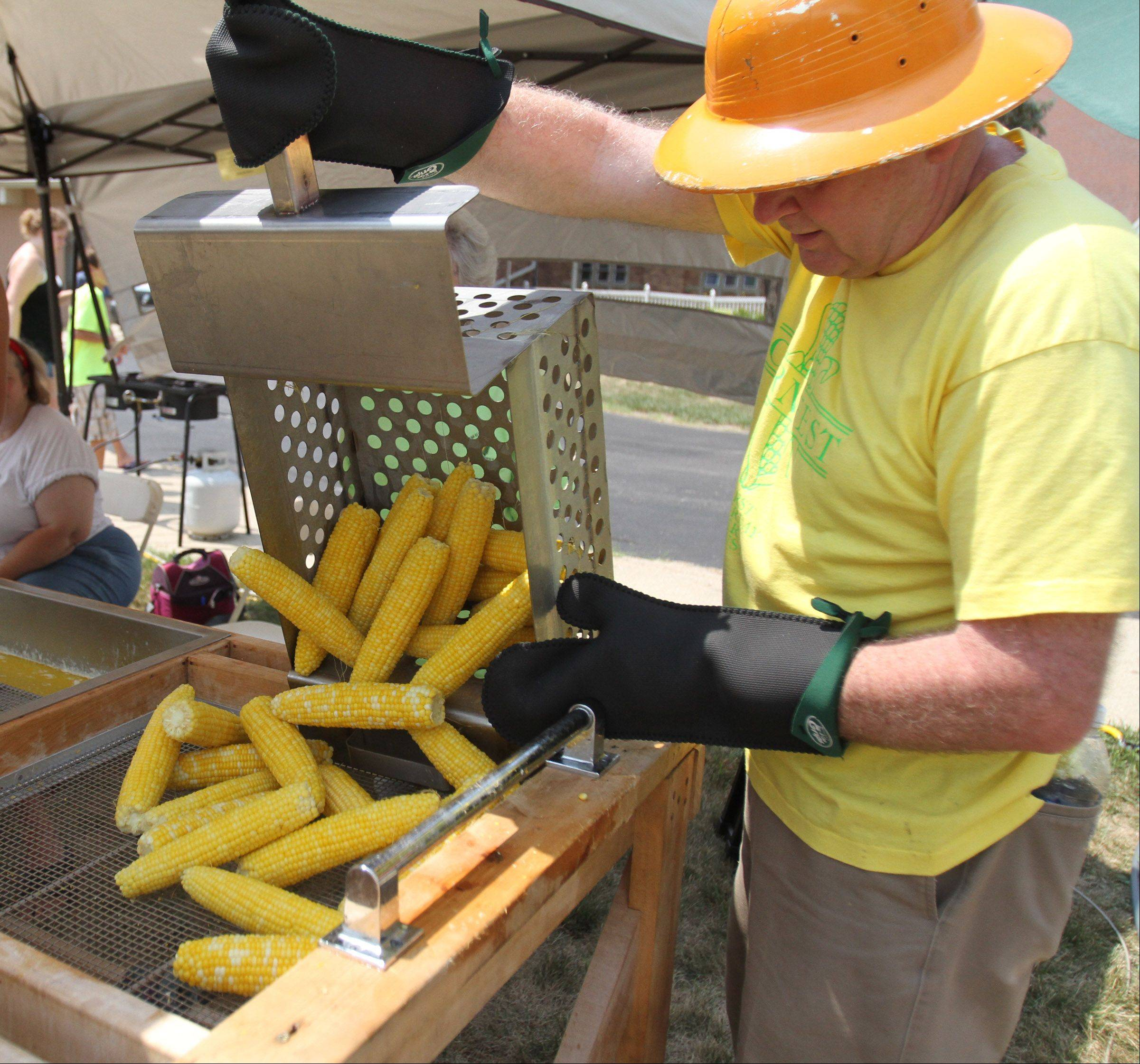 Richard Anderson of Rolling Meadows dumps a batch of boiled ears of corn into a butter bath area during Community Church of Rolling Meadows 56th Annual Cornfest Saturday.