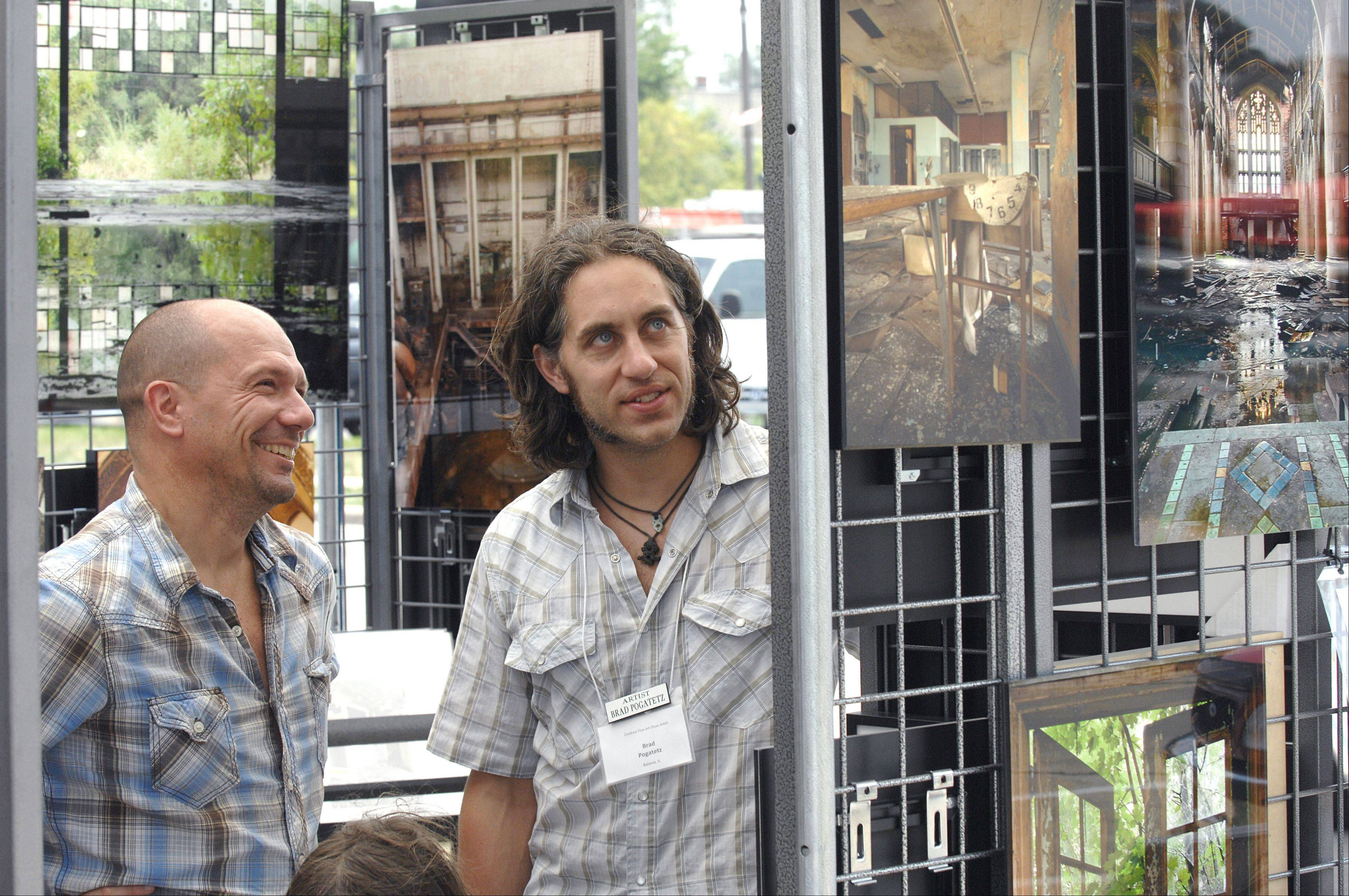 Batavia photographer Brad Pogatetz, right, talks about his work with Jon Schlenker, also of Batavia, at the Art in Your Eye festival along the town's Riverwalk Saturday. This is Pogatetz' second year in the show. His work focuses on abandoned buildings, mainly in the Midwest, and the items left behind in them, with some buildings being reclaimed by nature.