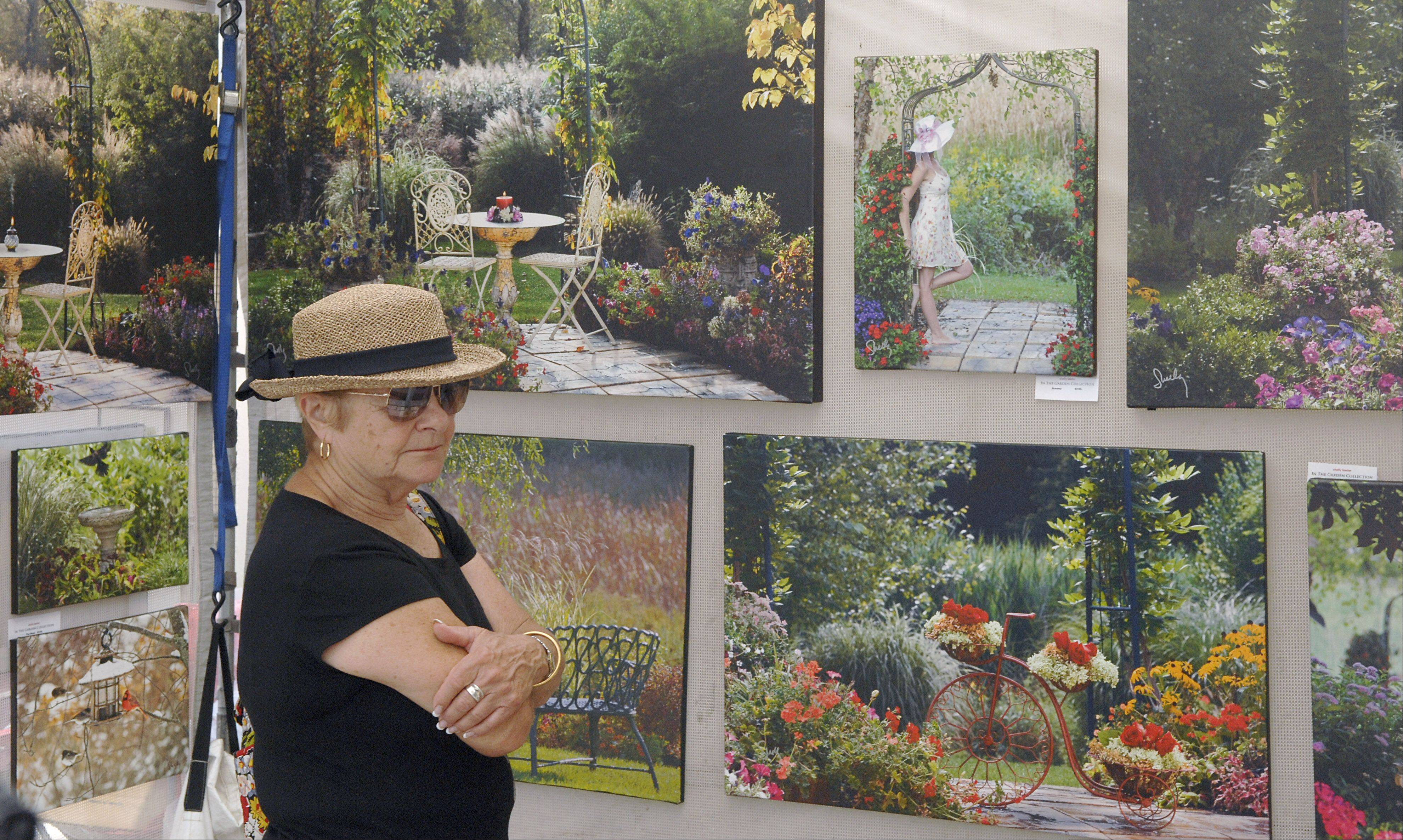 "Sandra Smith of Geneva looks at the ""In the Garden Collection"" photography series by Hoffman Estates photographer Shelly Lawler at Batavia's Art in Your Eye festival along the Batavia Riverwalk Saturday. Lawler photographs the series in her own backyard garden."