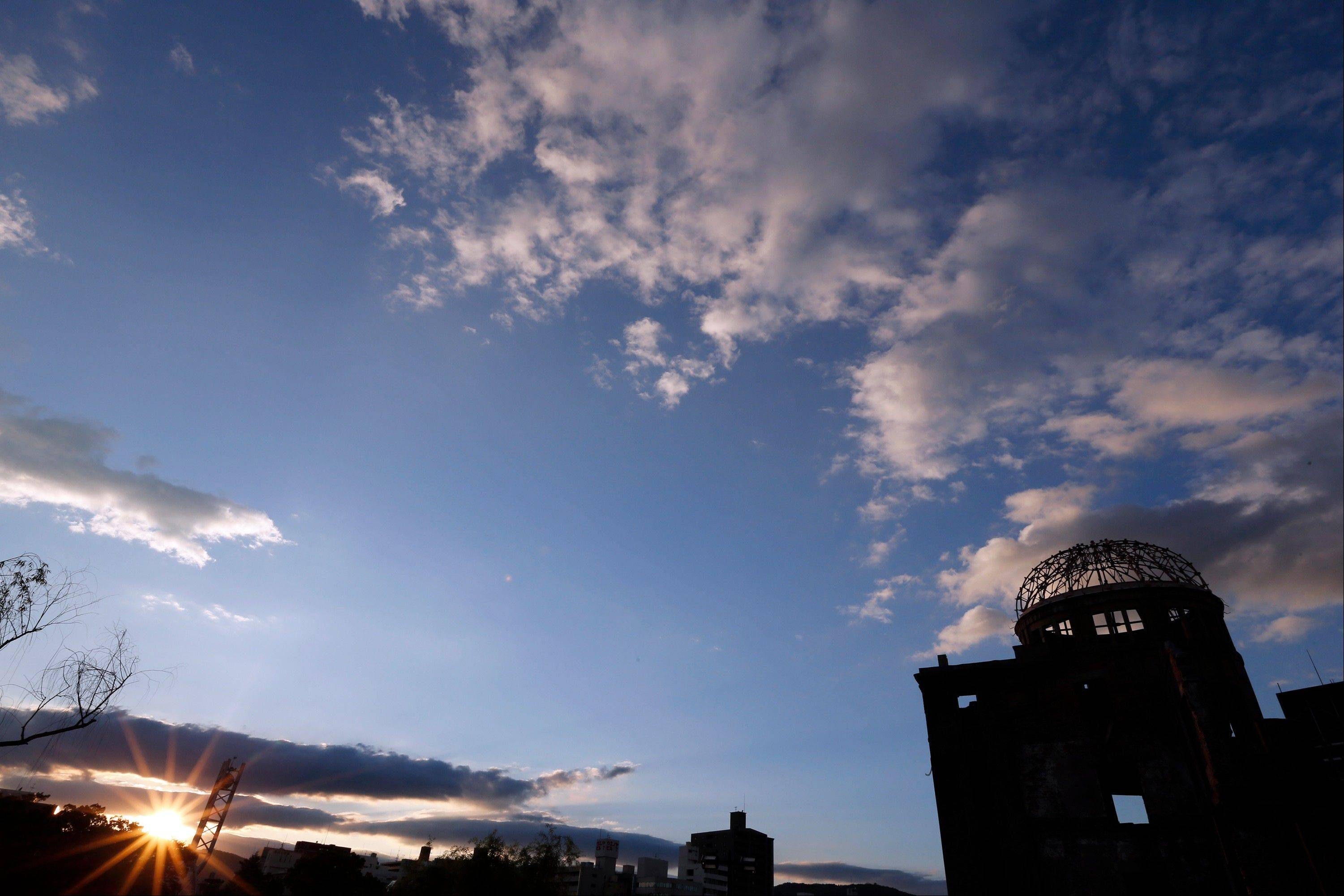 The sun sets by the gutted Atomic Bomb Dome, right, in Hiroshima, western Japan, Saturday, Aug. 4, 2012. Hiroshima marks the 67th anniversary of the atomic bombing on Aug. 6.