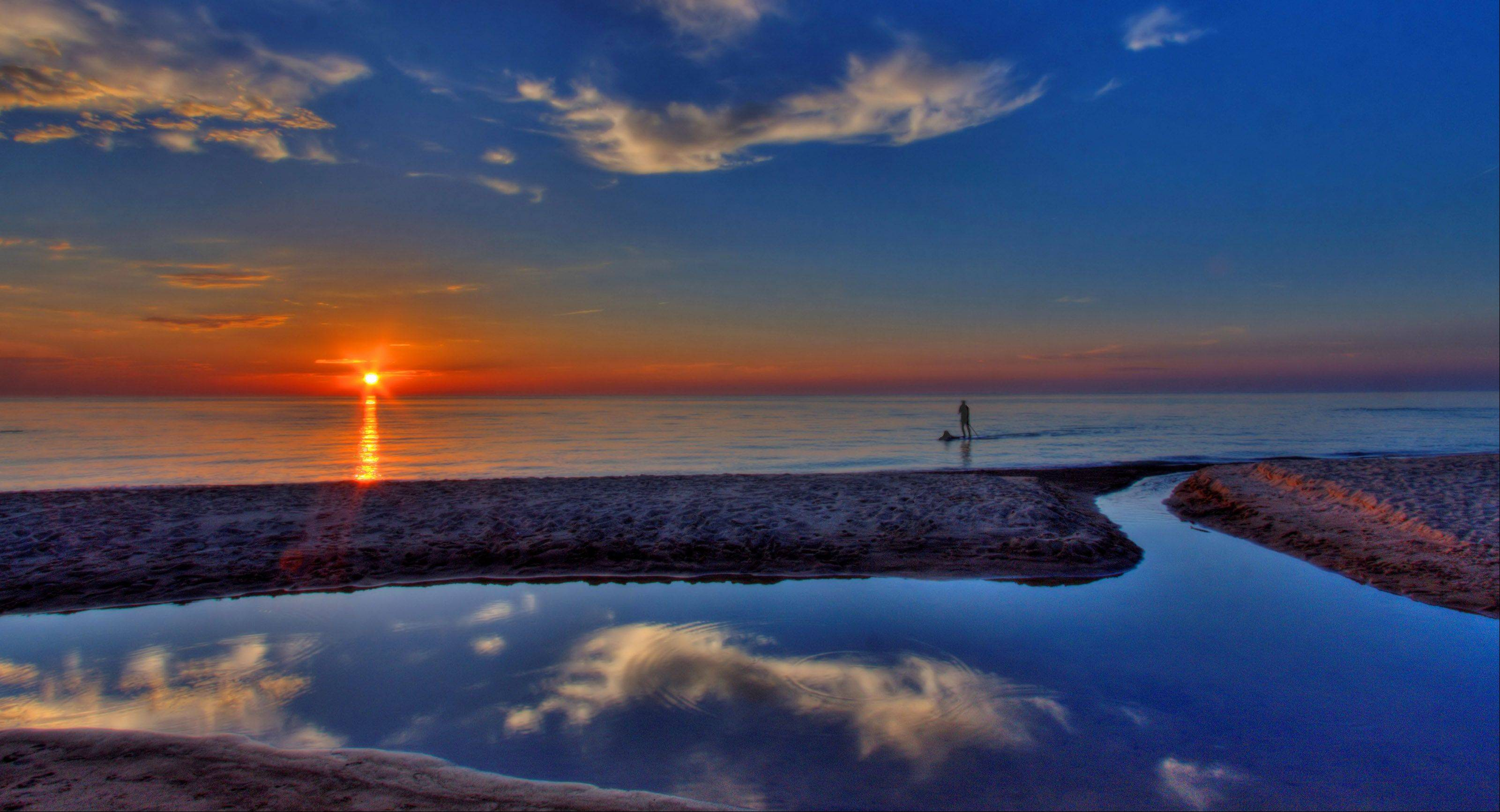 "Leo Modica of Wheaton took this photo of a paddler on the edge of Lake Michigan during a sunset. ""It was an interesting photo where the subject was the paddler but also the sun, and I like those pictures because they show humans in nature,"" he said."