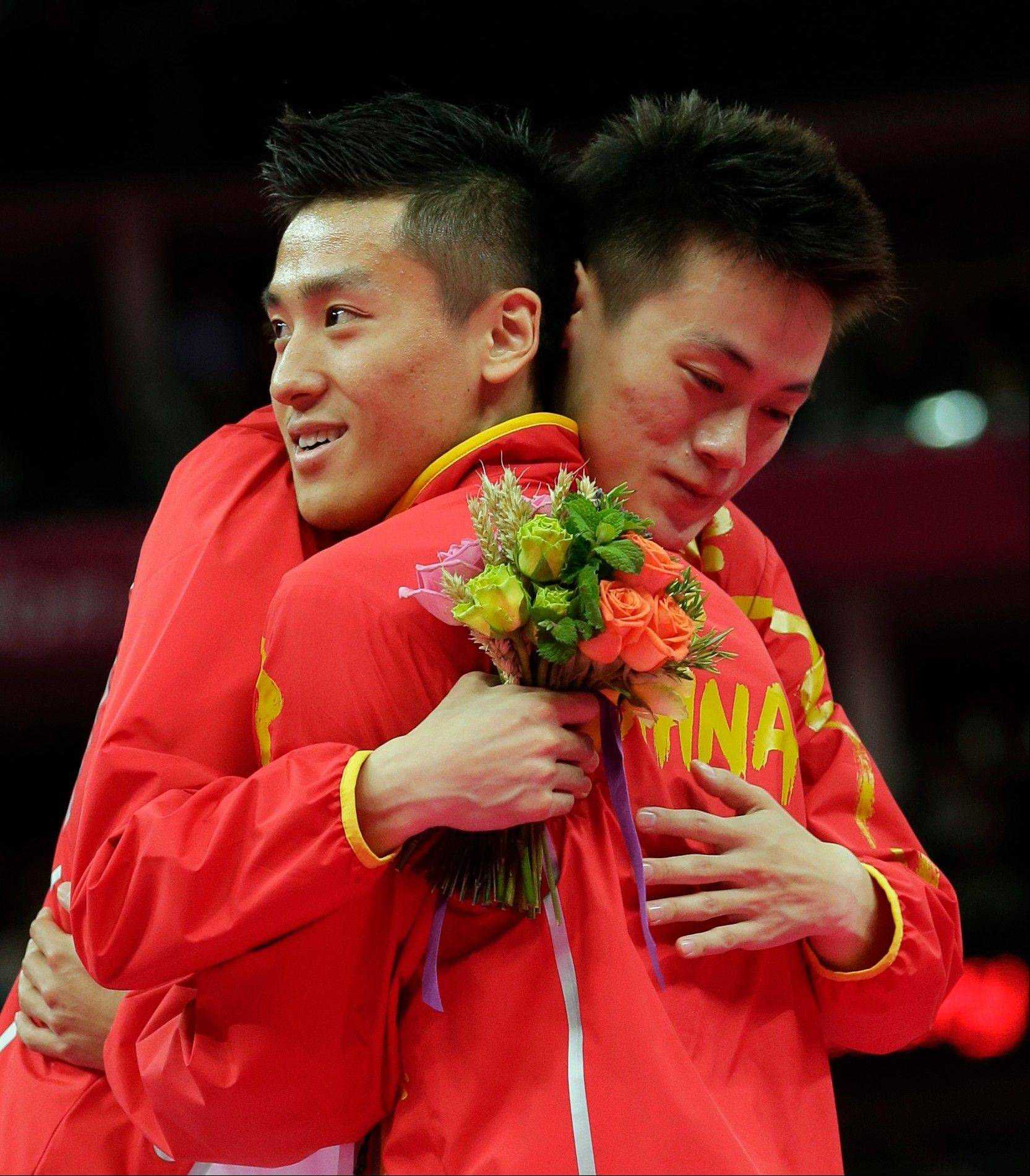 Gold medallist China's Dong Dong, right, and teammate bronze medallist Lu Chunlong hug during the medal ceremony of the men's trampoline finals at the 2012 Summer Olympics, Friday, Aug. 3, 2012, in London.