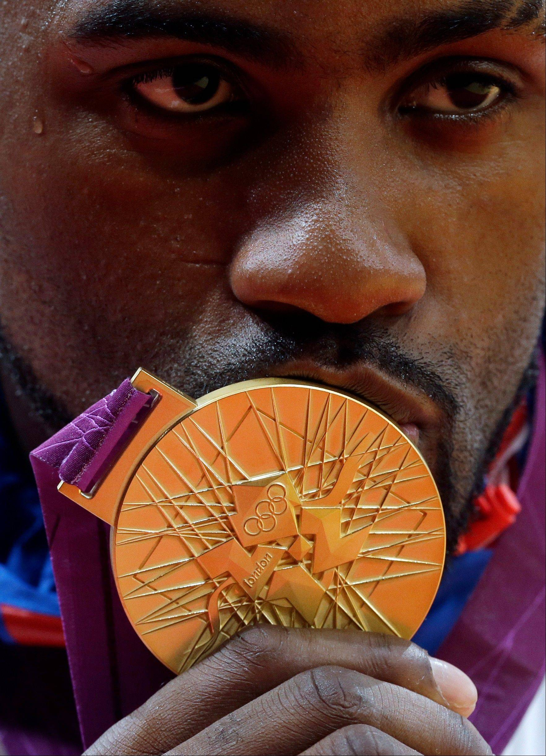 France's Teddy Riner kisses his gold medal for the men's over 100-kg judo competition at the 2012 Summer Olympics, Friday, Aug. 3, 2012, in London.