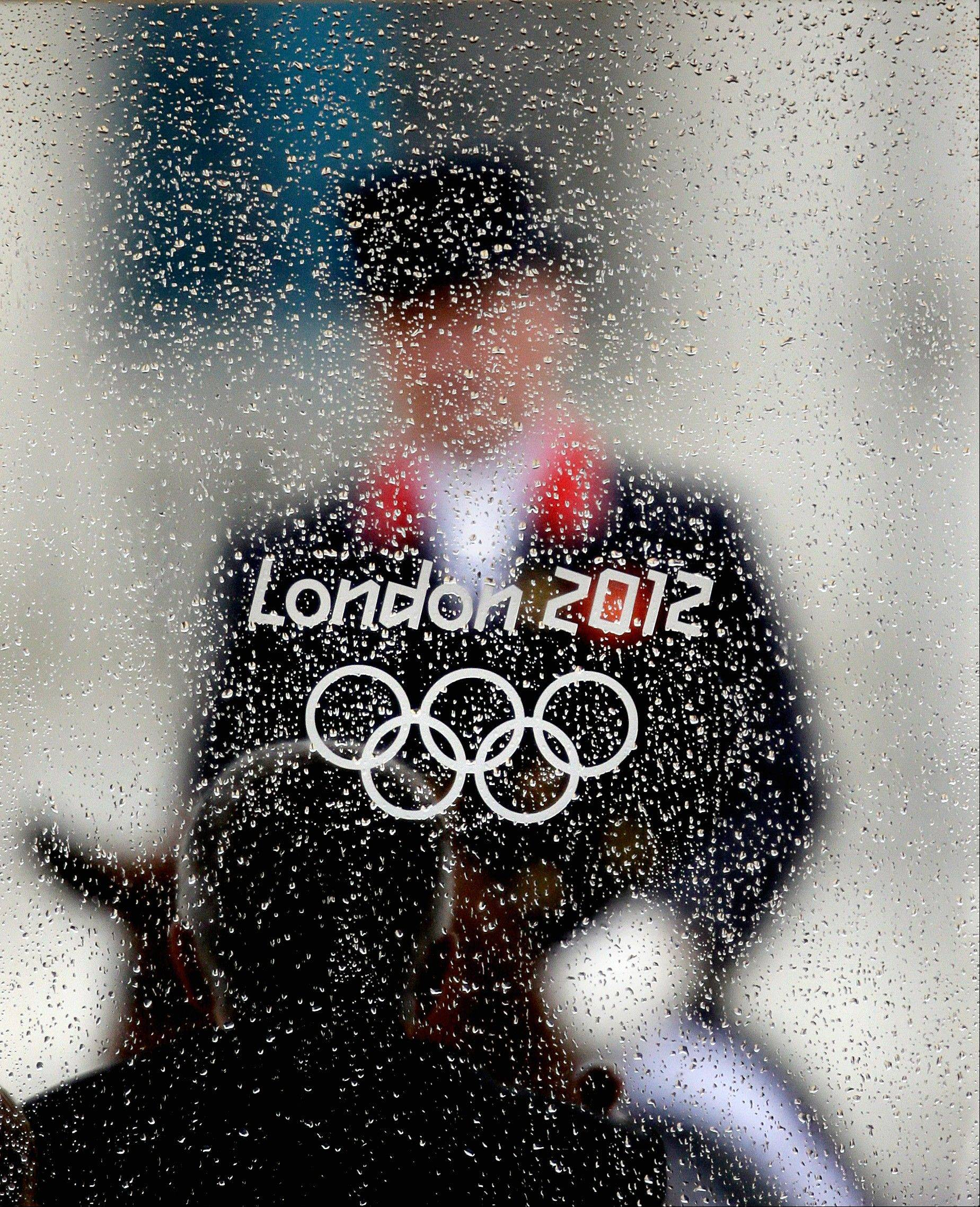 Rain drops collect on the window of a judge's booth as Richard Davison, of Great Britain, rides his horse Artemis, in the equestrian dressage competition at the 2012 Summer Olympics, Friday, Aug. 3, 2012, in London.