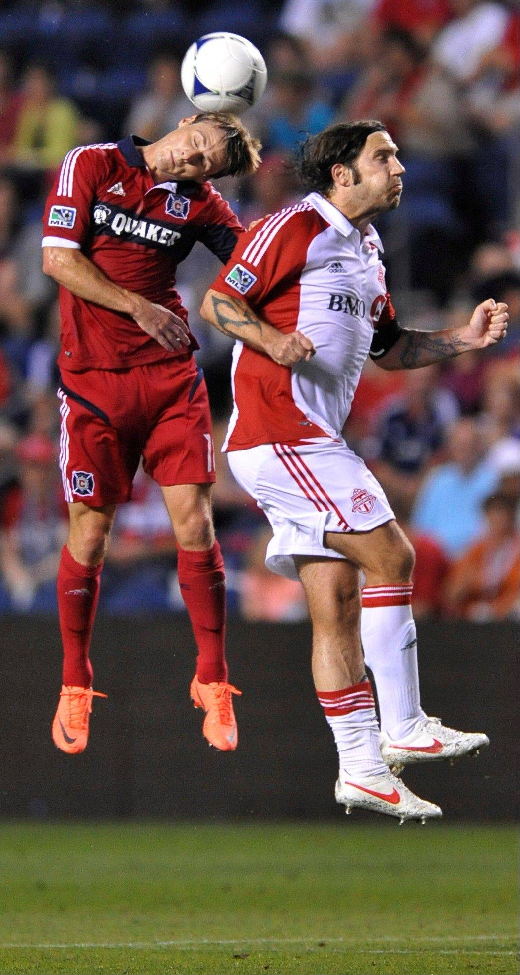 Chicago Fire's Chris Rolfe left, goes up for a header against Toronto FC's Torsten Frings in the first half of an MLS soccer game in Bridgeview, Ill., Saturday, Aug. 4, 2012.