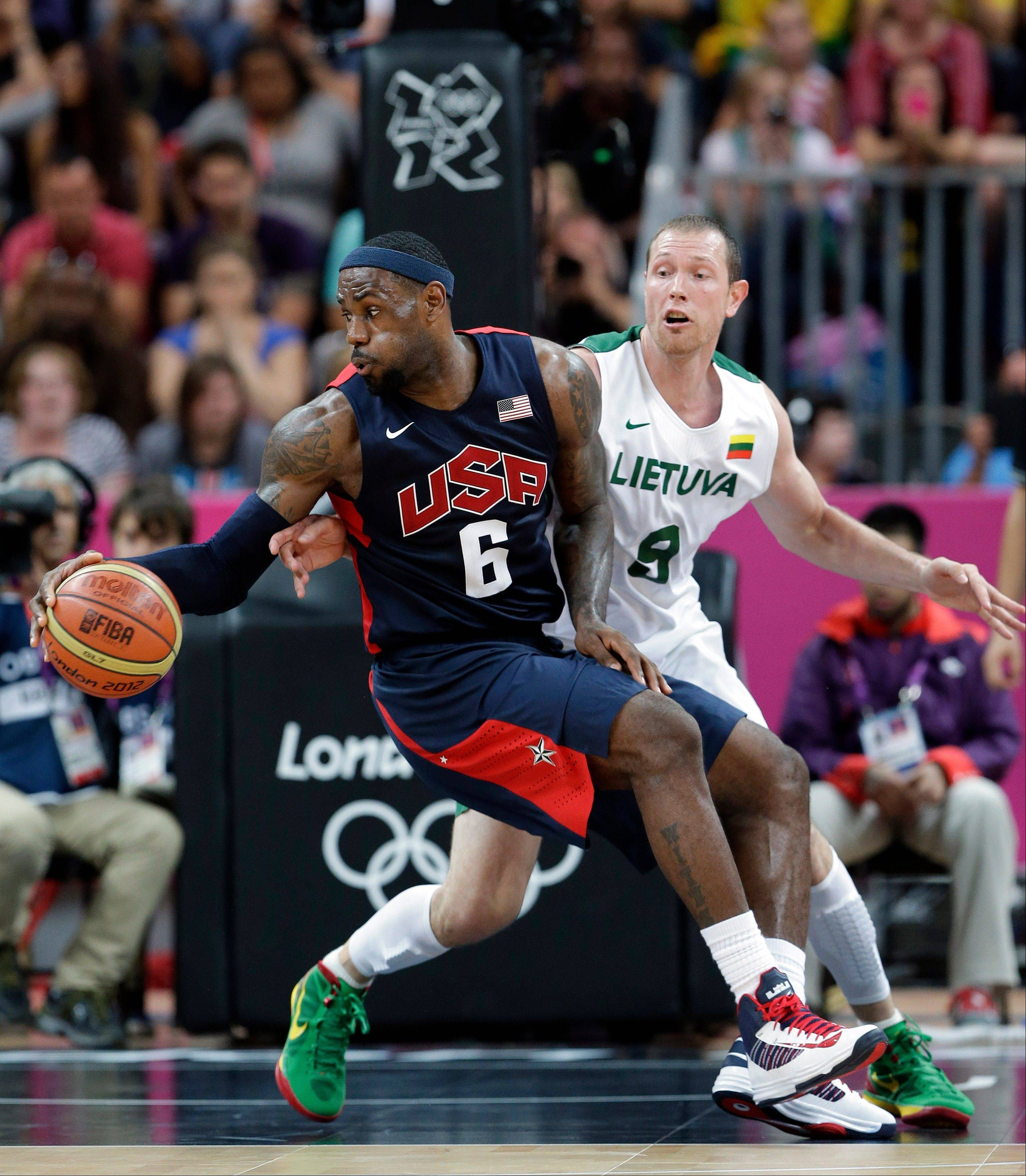 USA forward LeBron James works the ball past Lithuania's Renaldas Seibutis Saturday during a preliminary men's basketball game at the 2012 Summer Olympics.