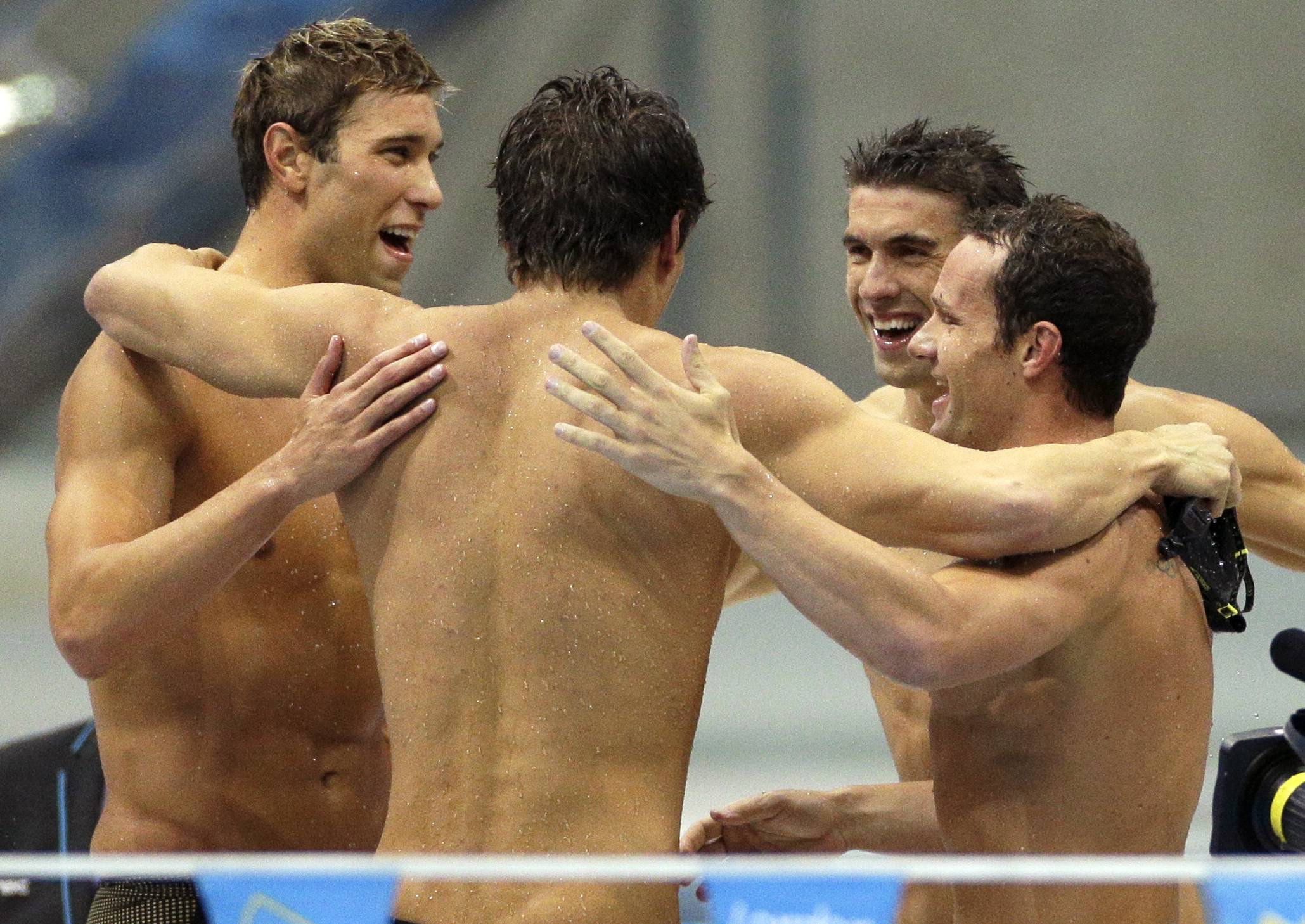The United States' men's 4 X 100-meter medley relay team from left, Matthew Grevers, Nathan Adrian, Michael Phelps and Brendan Hansen embrace after winning the gold medal at the Aquatics Centre.
