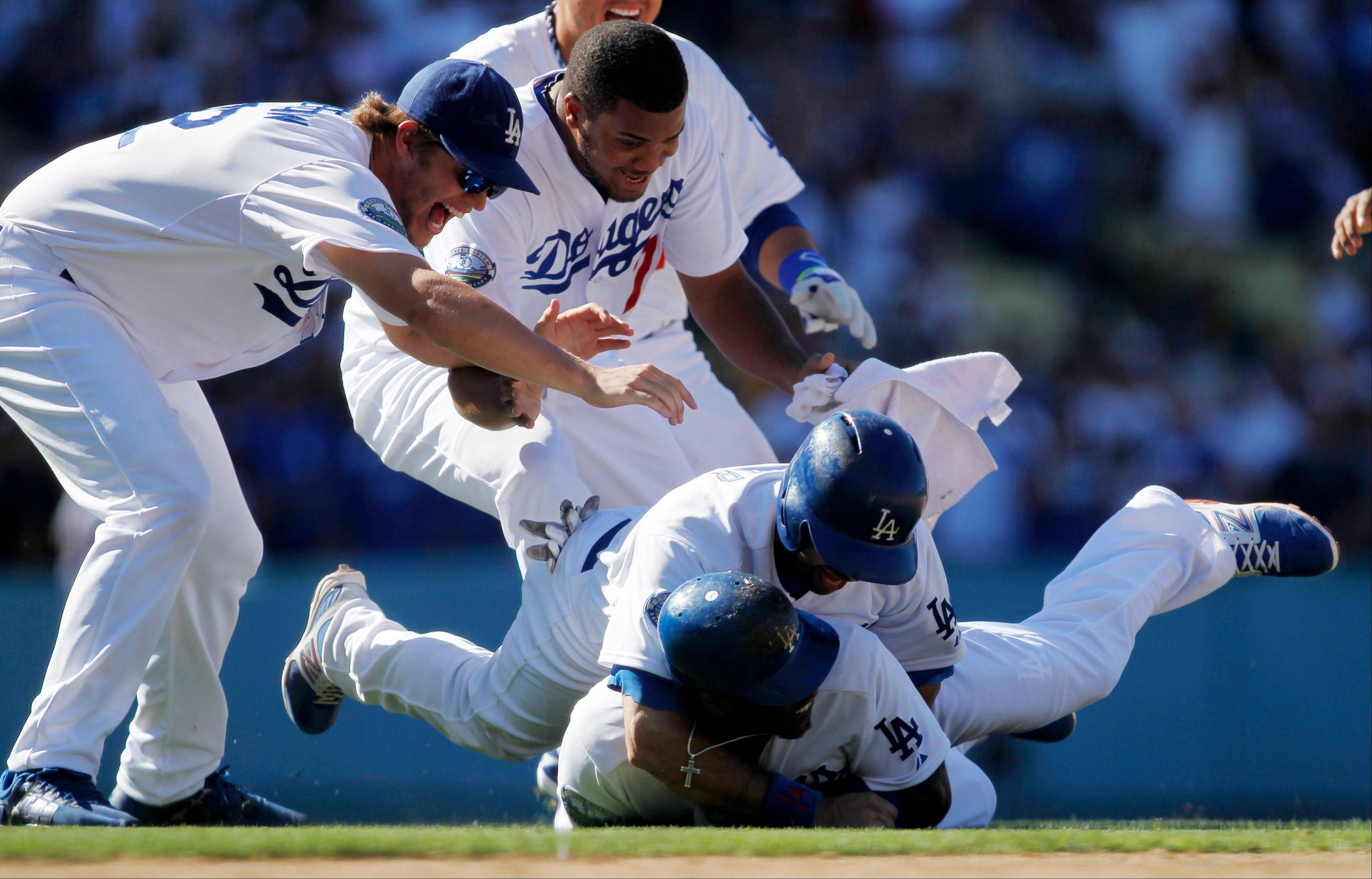 Los Angeles Dodgers slugger Hanley Ramirez, bottom, is mobbed by teammates including, from left to right, Clayton Kershaw, Kenley Jansen and Andre Ethier after he knocked in the game-winning run Sunday against the Cubs at Dodgers Stadium.