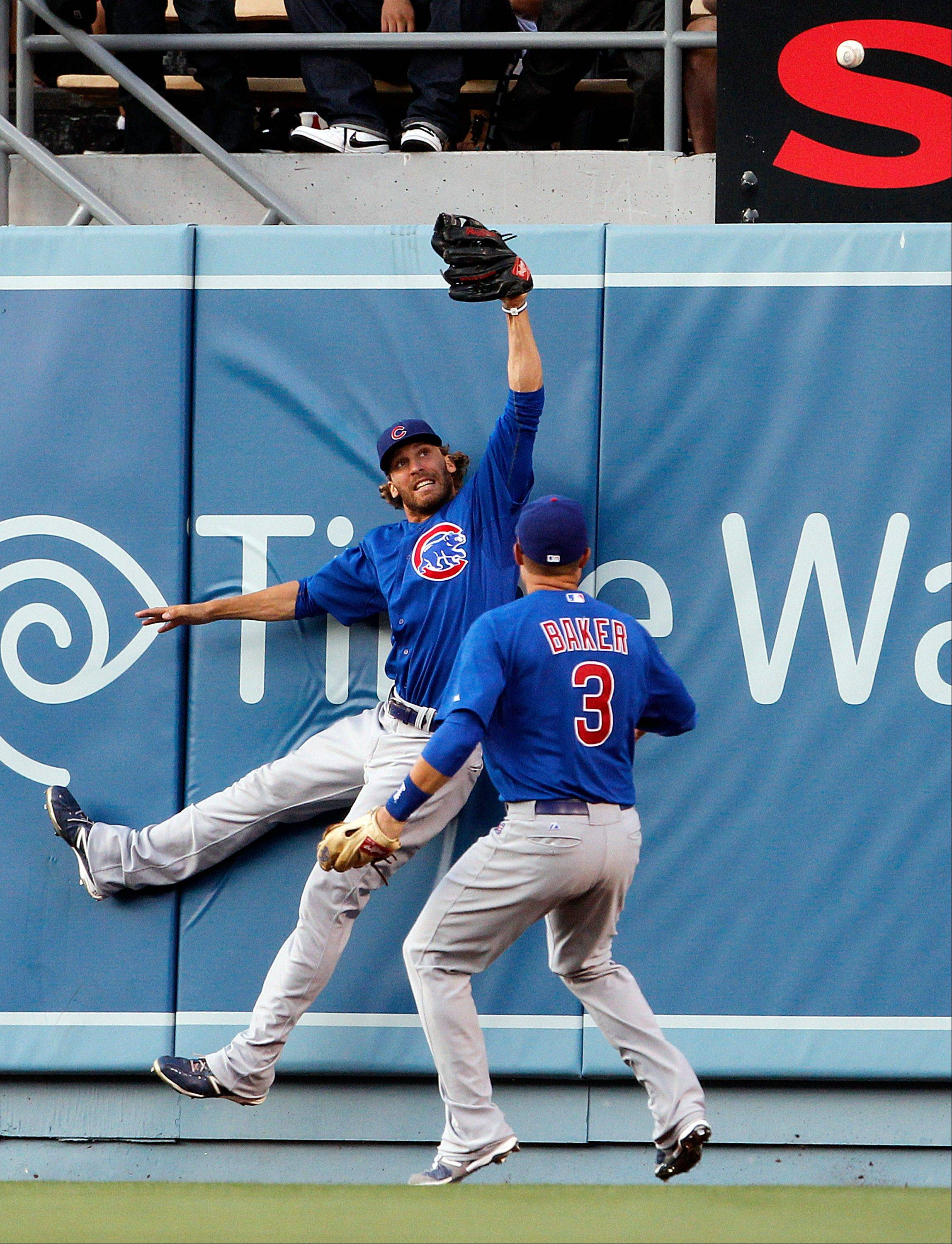 Cubs center fielder Joe Mather, left, and right fielder Jeff Baker can't reach a home run by the Los Angeles Dodgers' Matt Kemp Saturday during the fourth inning.