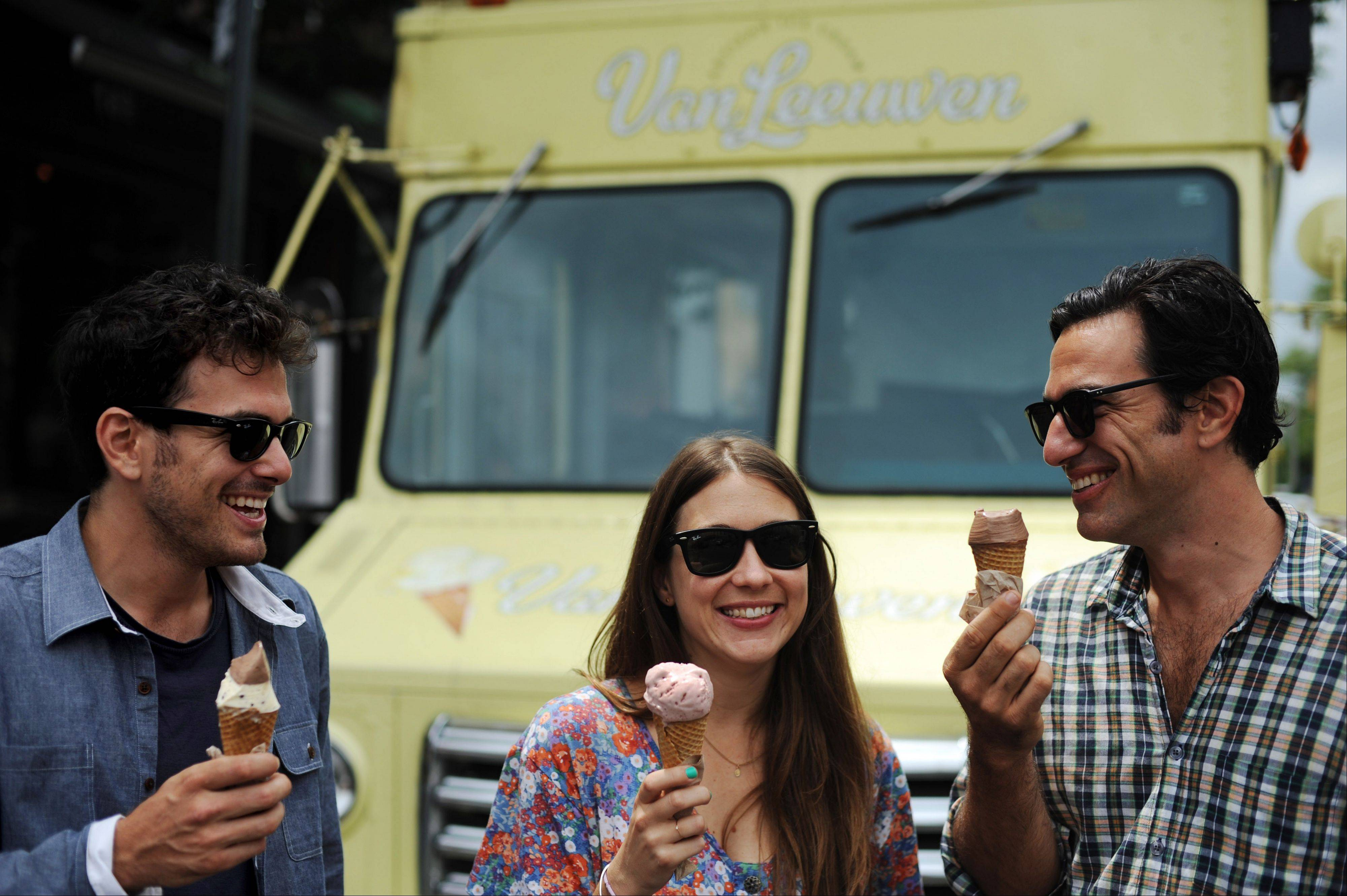 Van Leeuwen Artisan Ice Cream co-owners Ben Van Leeuwen, Laura O'Neill and Pete Van Leeuwen laugh while talking about the origins of their business while eating ice cream in front of one of their trucks on Bedford Avenue in the Williamsburg section of New York's Brooklyn borough.