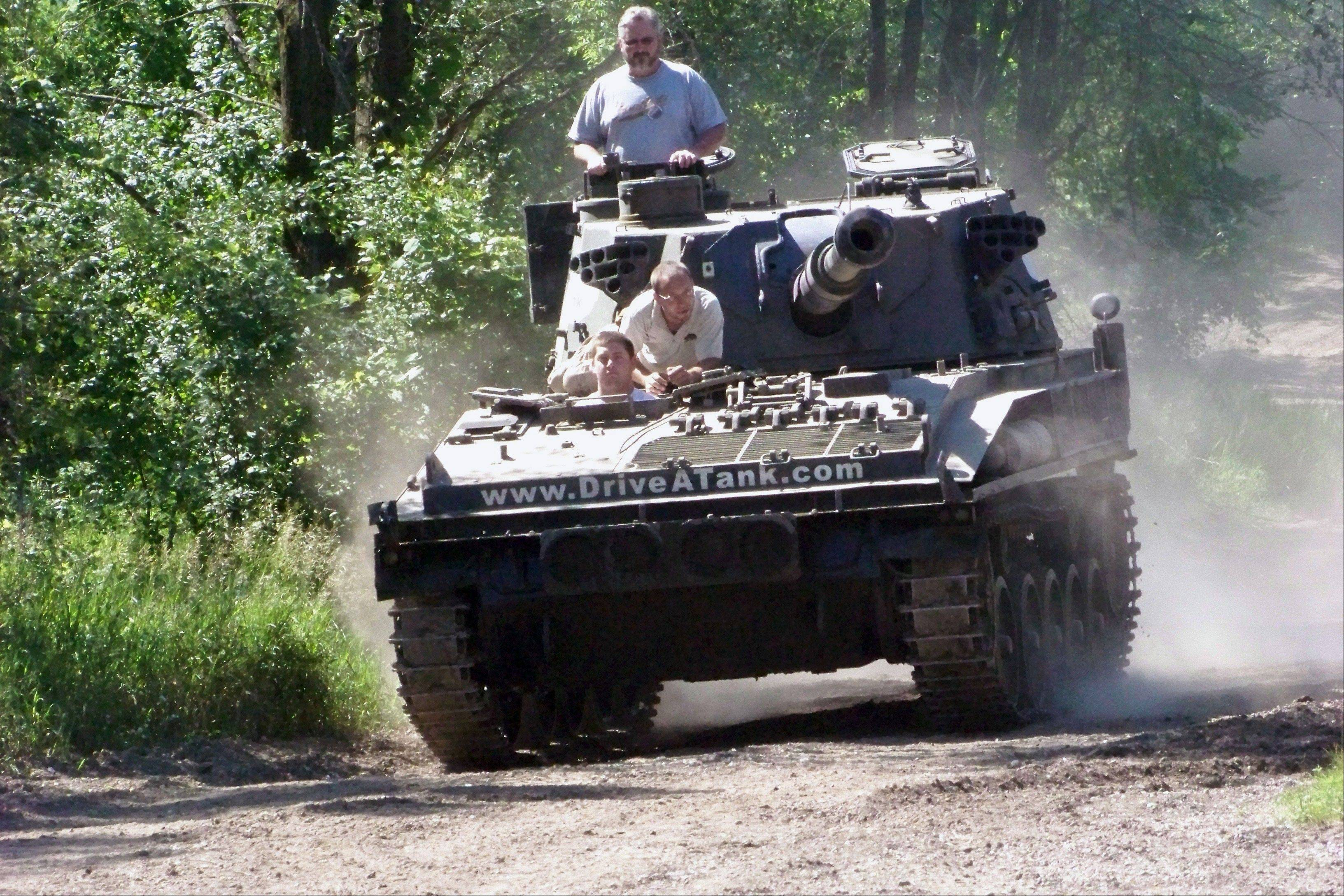 Nick Walker of Amboy, Ind., drives a tank in Kasota, Minn., while his father Brad Walker looks out from the turret and Drive-A-Tank owner Tony Borglum sits behind him.