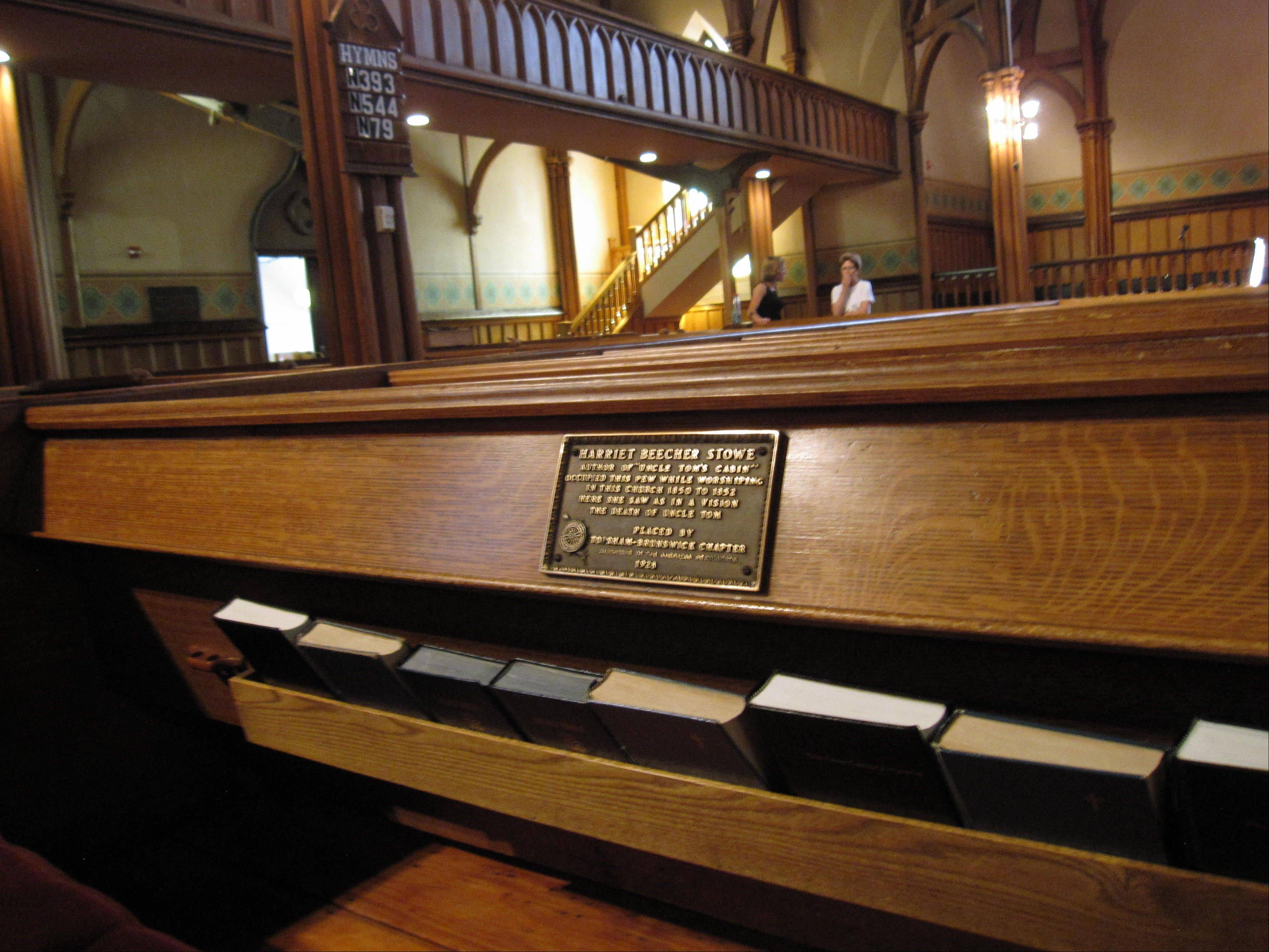 "A marker on a pew at First Parish Church in Brunswick, Maine, shows where ""Uncle Tom's Cabin"" author Harriet Beecher Stowe sat in 1851 when she had a vision of a scene for the book. The church, a Gothic Revival building that dates to the 1840s, is one of 14 sites in Brunswick on the National Register of Historic Places."