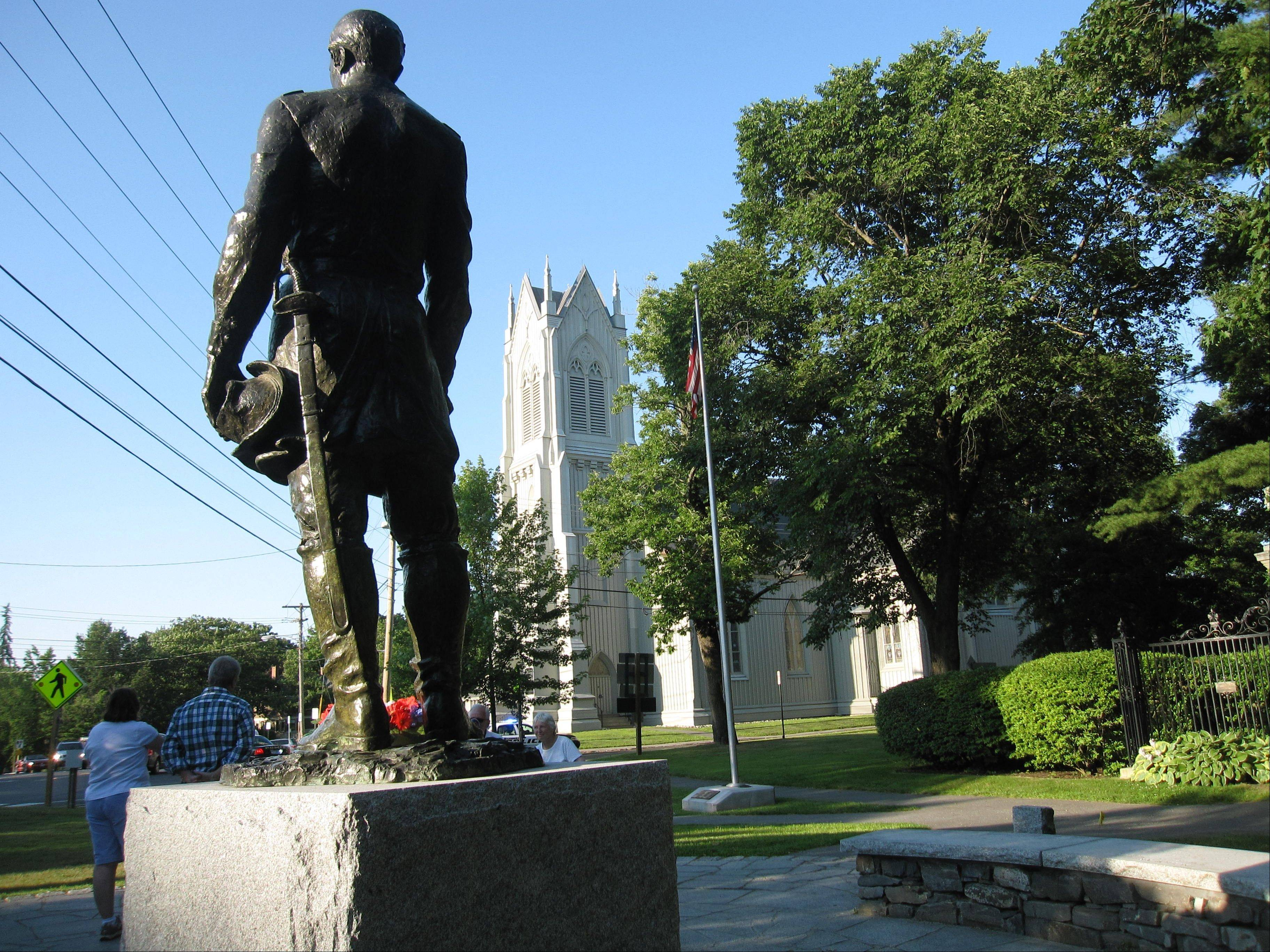 Behind the statue of Joshua Chamberlain sits the First Parish Church, a Gothic Revival building that dates to the 1840s.
