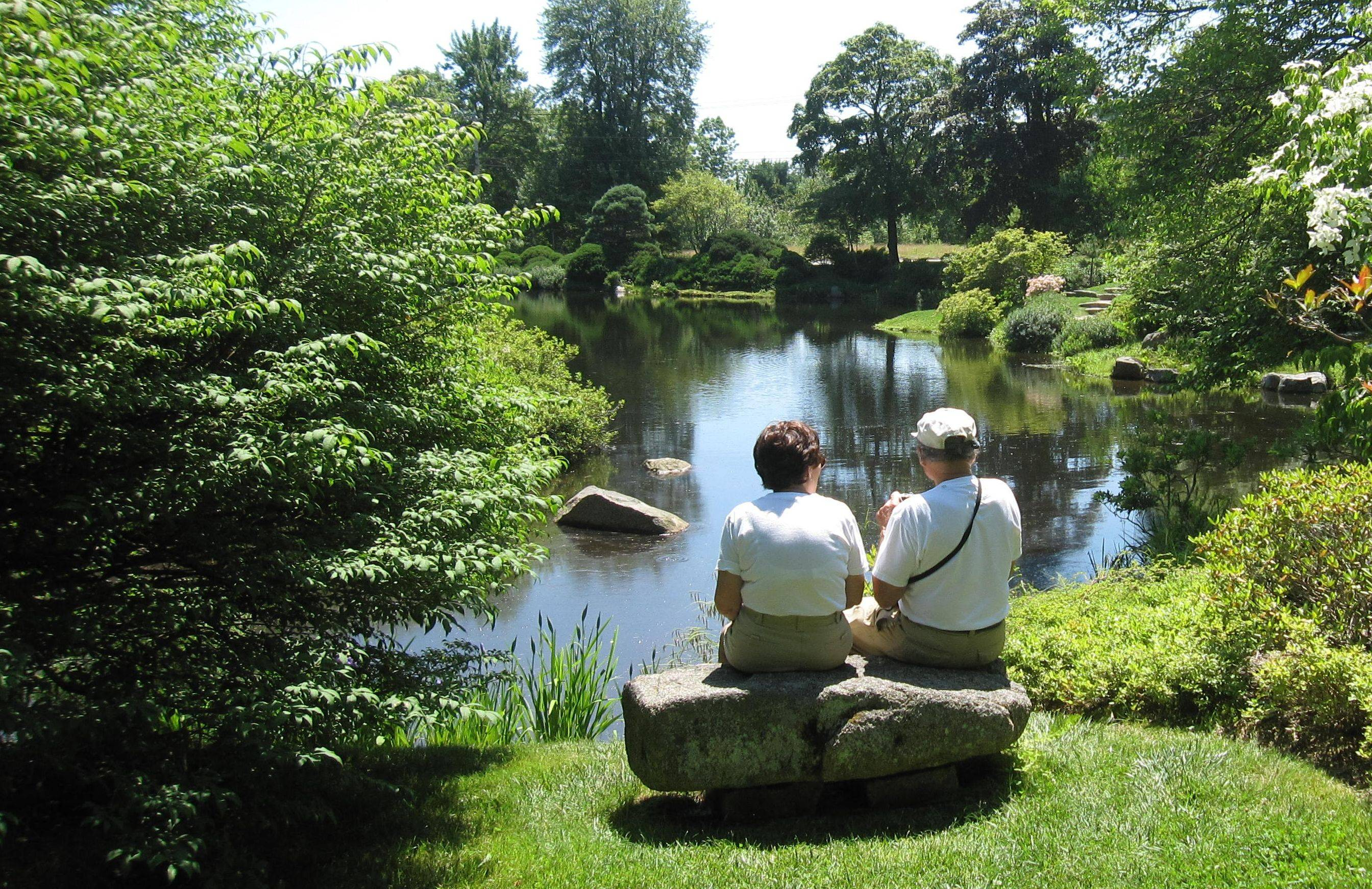 Visitors sit on a rock bench to view the scenery at the Asticou Azalea Garden pond in Northeast Harbor, Maine. The garden includes plants from noted landscape designer Beatrix Farrand, who has designed gardens for the White House and prominent clients such as John D. Roosevelt and his wife, Abby.