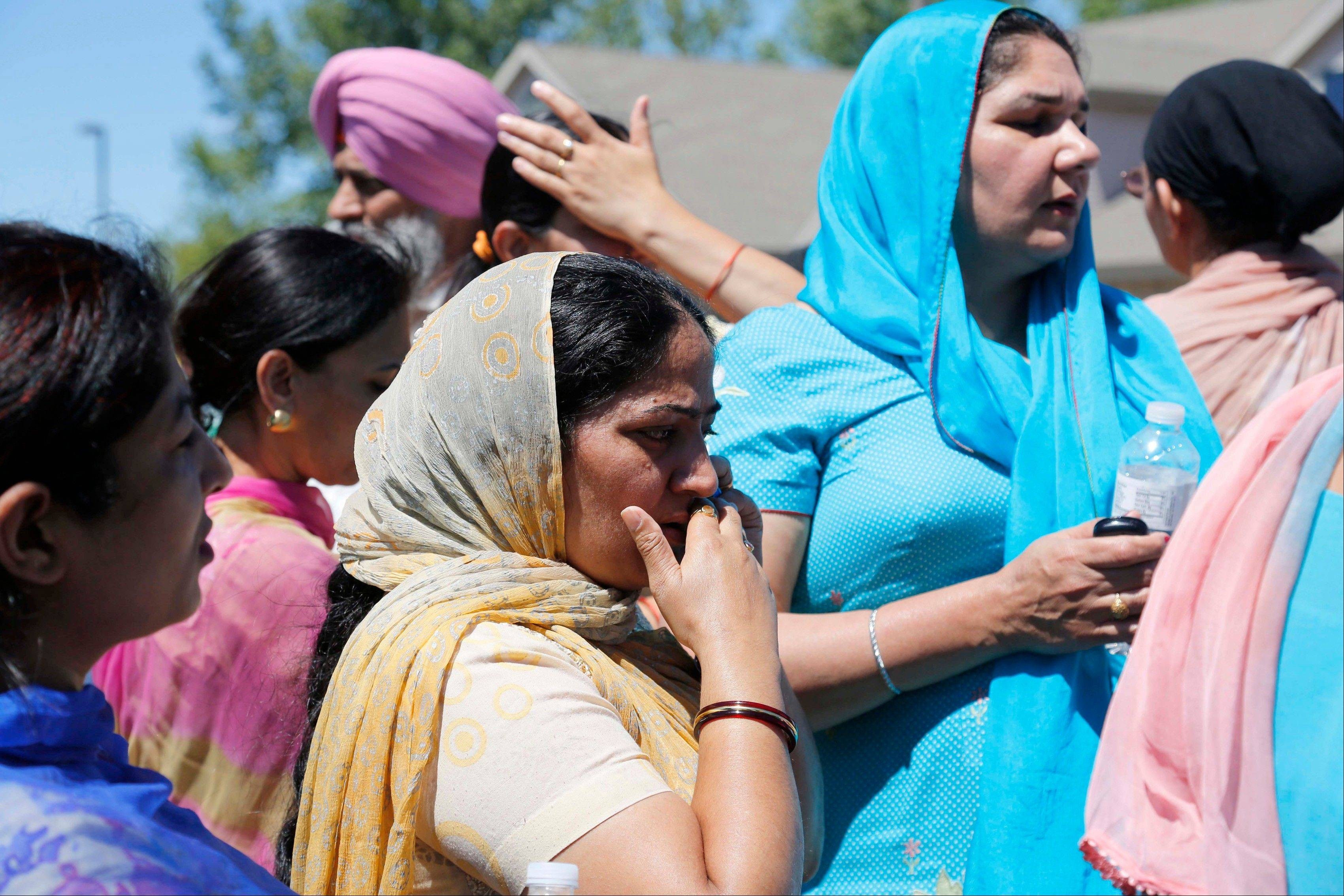 Bystanders assemble outside the scene of a shooting inside a Sikh temple in Oak Creek, Wis, on Sunday.