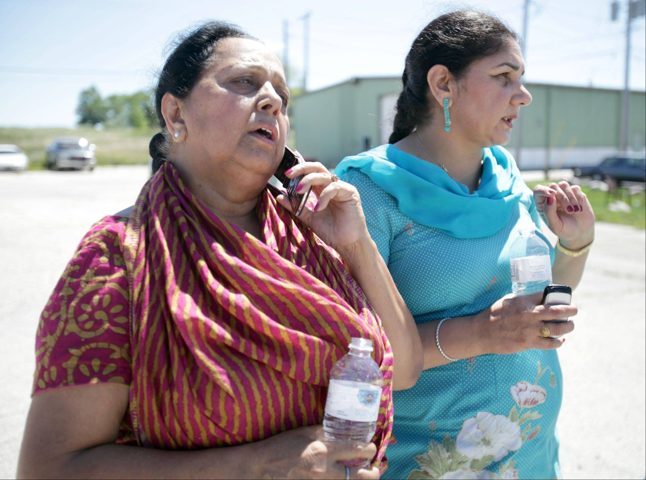 Parminder Kaleka, left, who said her brother-in-law was in the Sikh temple in Oak Creek, Wis., where a shooting occurred, uses a phone to try to get more information on Sunday.