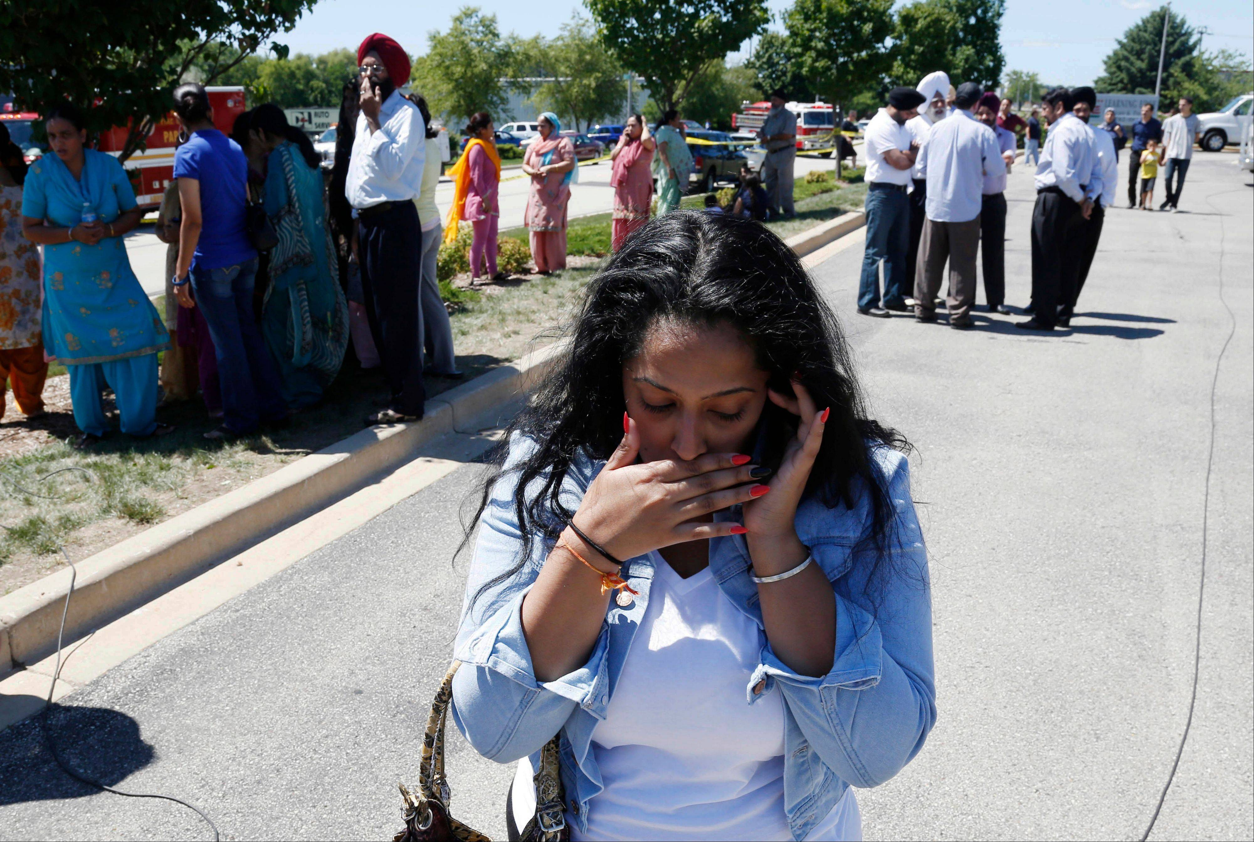 A woman reacts with others as they await word on a shooting at a Sikh temple in Oak Creek, Wis., on Sunday.